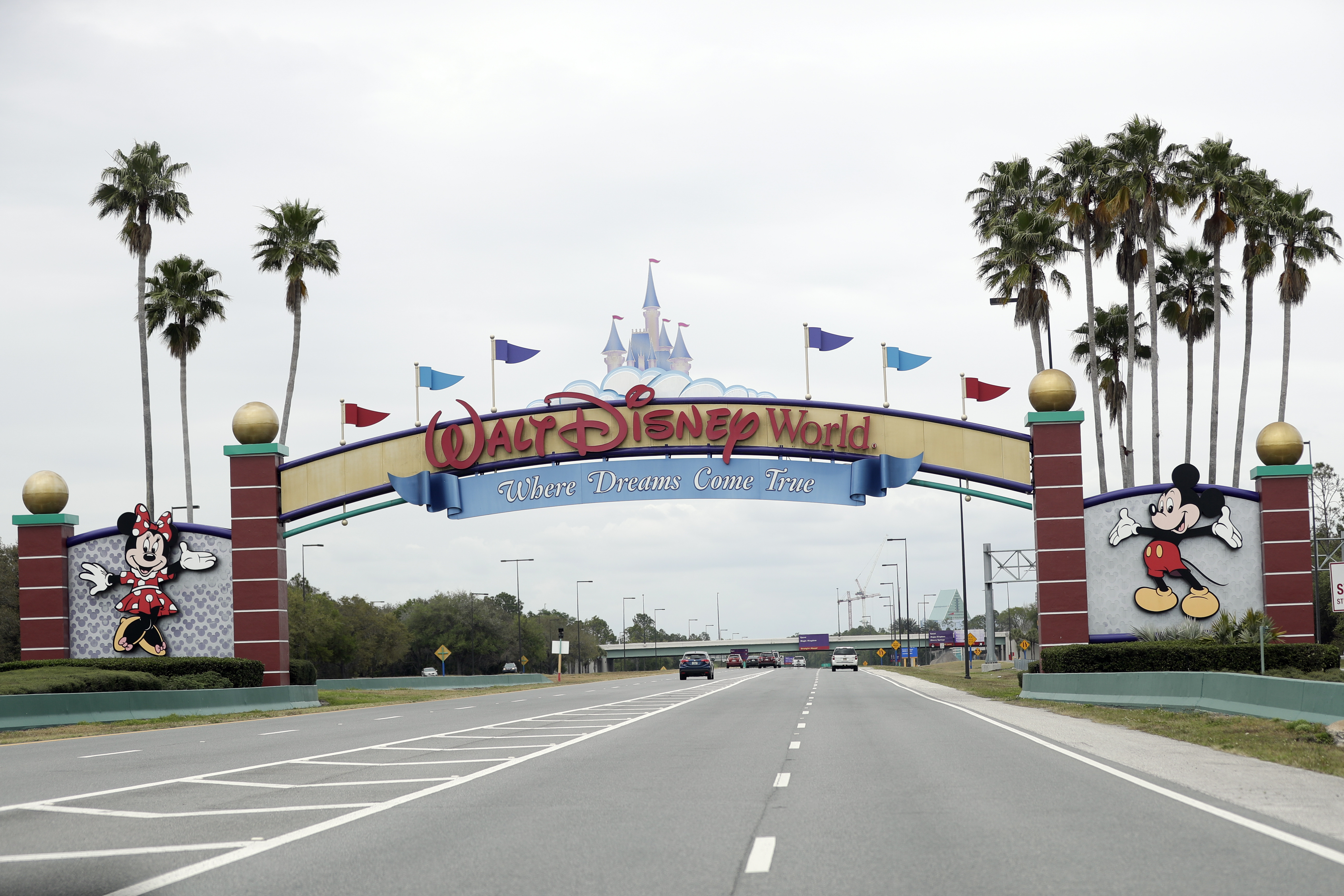 FILE - In this Monday, March 16, 2020, file photo, the road to the entrance of Walt Disney World has few cars, in Lake Buena Vista, Fla. Two more unions have reached agreements with Walt Disney World over furloughs caused by the theme park resort's closure during the new coronavirus outbreak. The agreements reached late Friday, April 10, apply to security guards and workers involved in facilities and operations. (AP Photo/John Raoux, File)