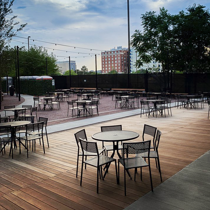 Small round tables sit distanced on a spacious outdoor patio, with some trees and tall buildings visible in the background