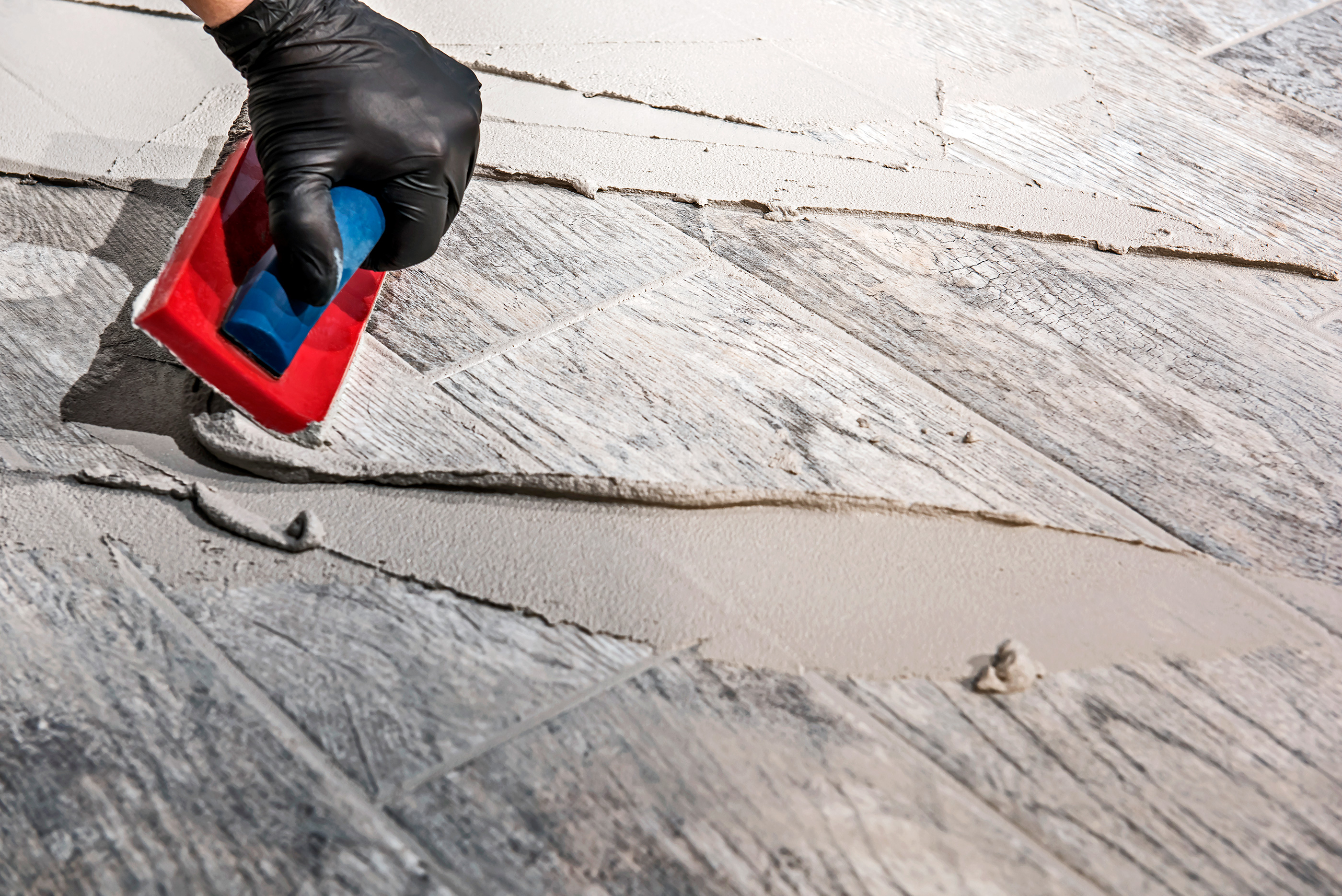 applying grout to a surface before tile