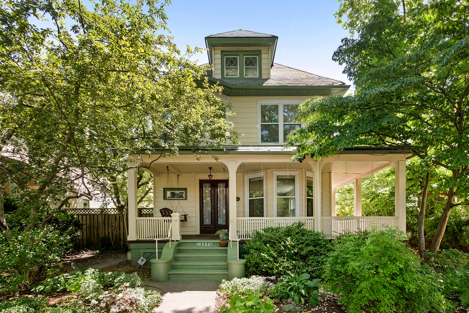 A Victorian home with eggshell-colored wood panels in its facade, green roofs, and a large porch.