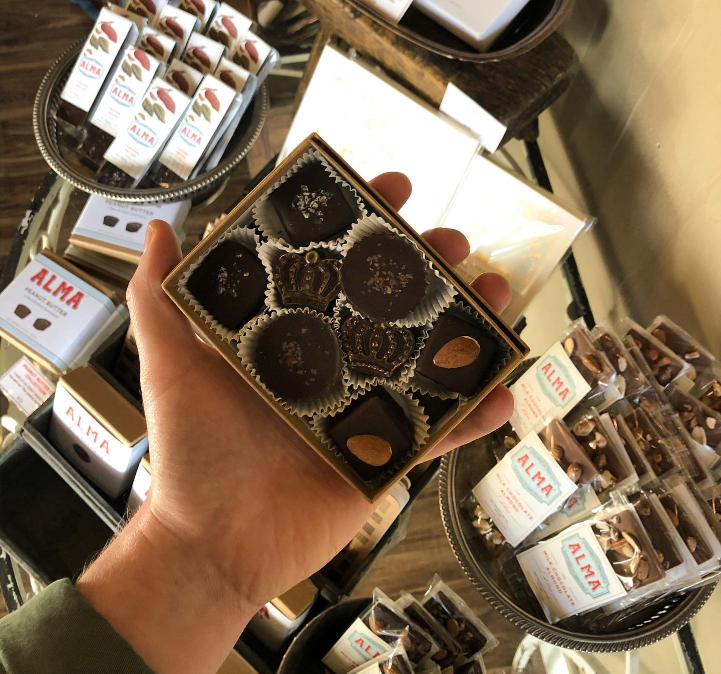 A hand holds up an open box of chocolate bon bons; in the background sit bowls containing Alma chocolate bars.