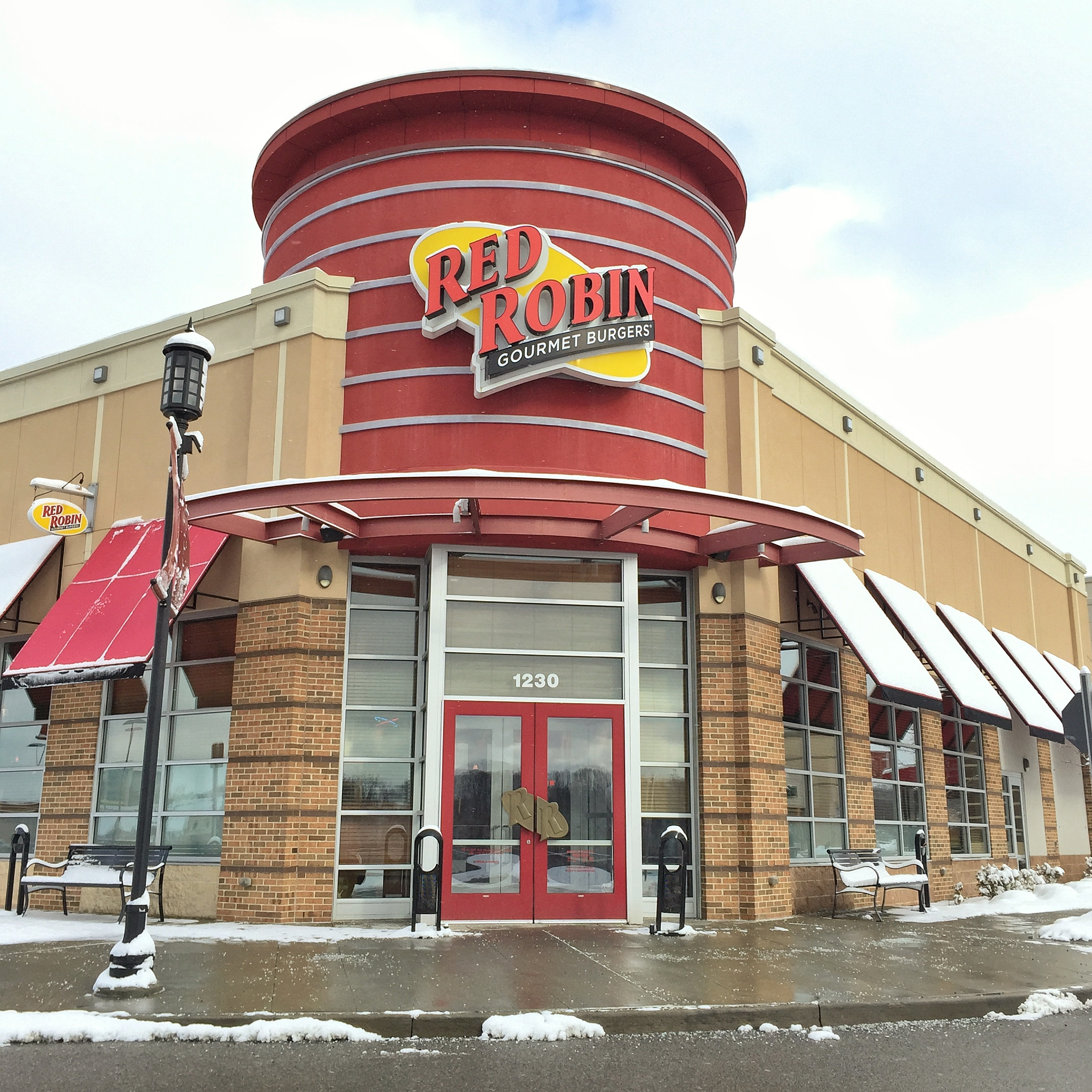 A Red Robin restaurant sign shown from the outside of a building on a cloudy day.