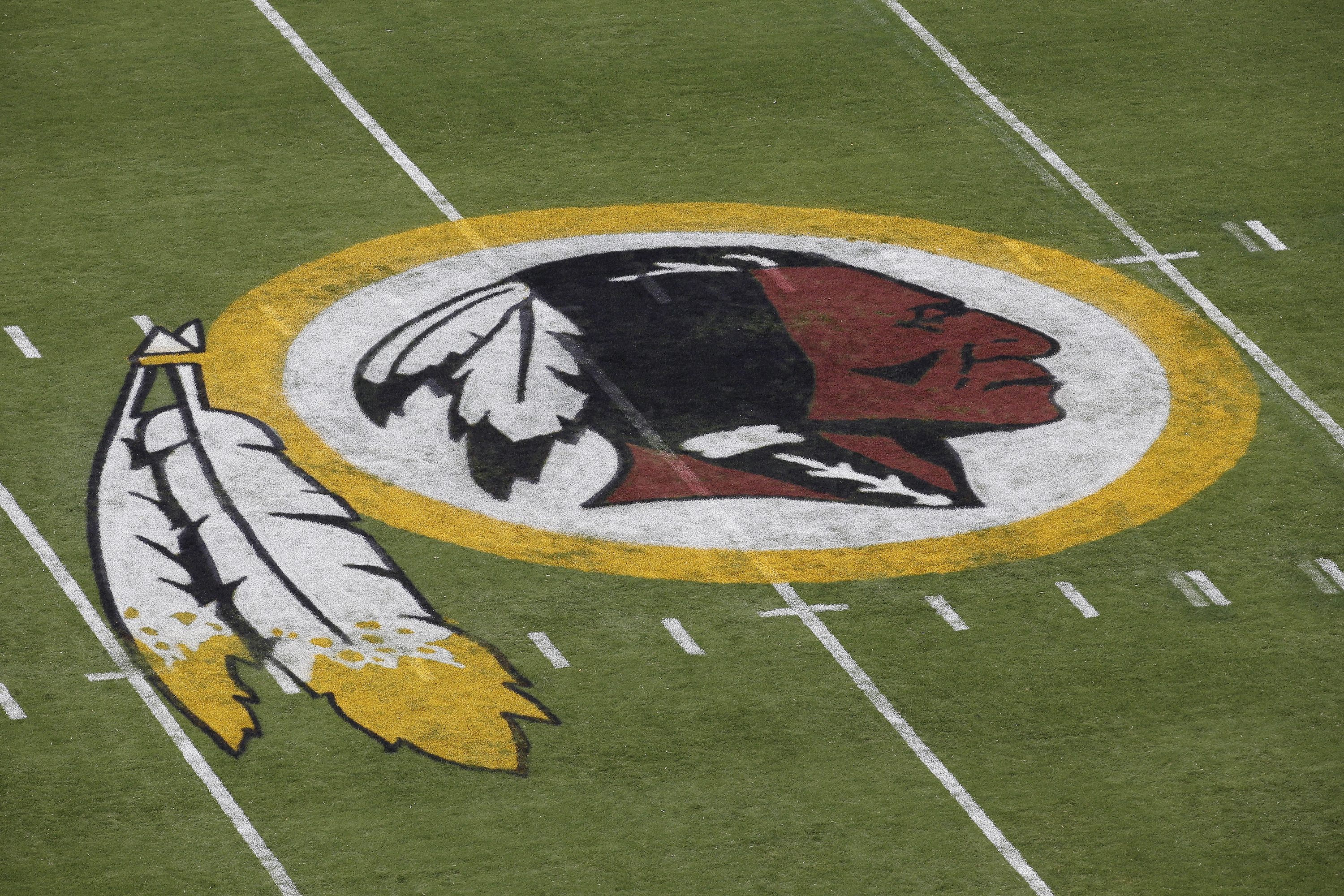 In this Aug. 7, 2014 file photo, the Washington Redskins NFL football team logo is seen on the field before an NFL football preseason game against the New England Patriots in Landover, Md.