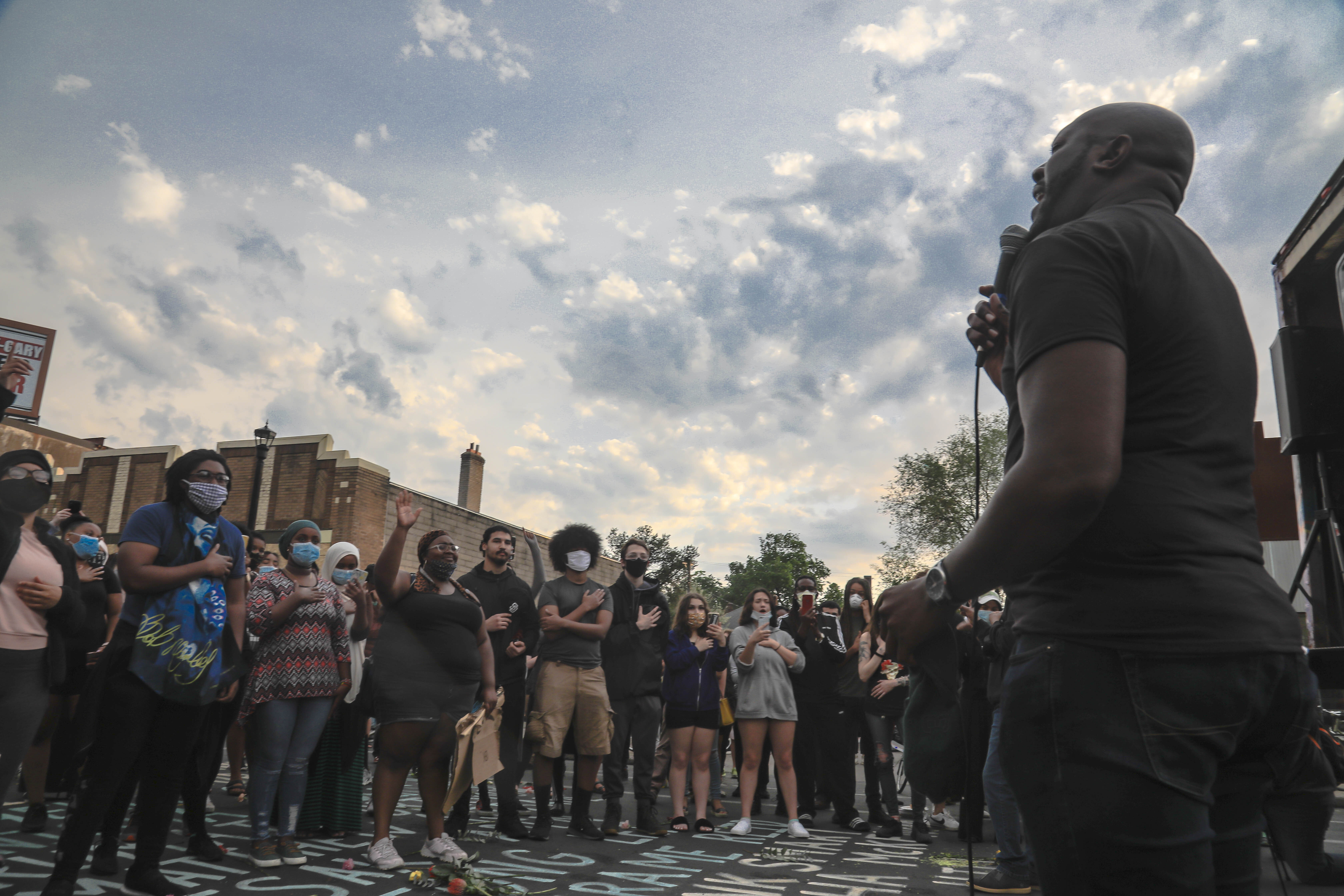 """People visiting the neighborhood where George Floyd was killed during an encounter with police, gather to listen as Rev. Mack Knight, right, sings the Black national anthem """"Lift Every Voice,"""" Tuesday, June 2, 2020, in Minneapolis."""