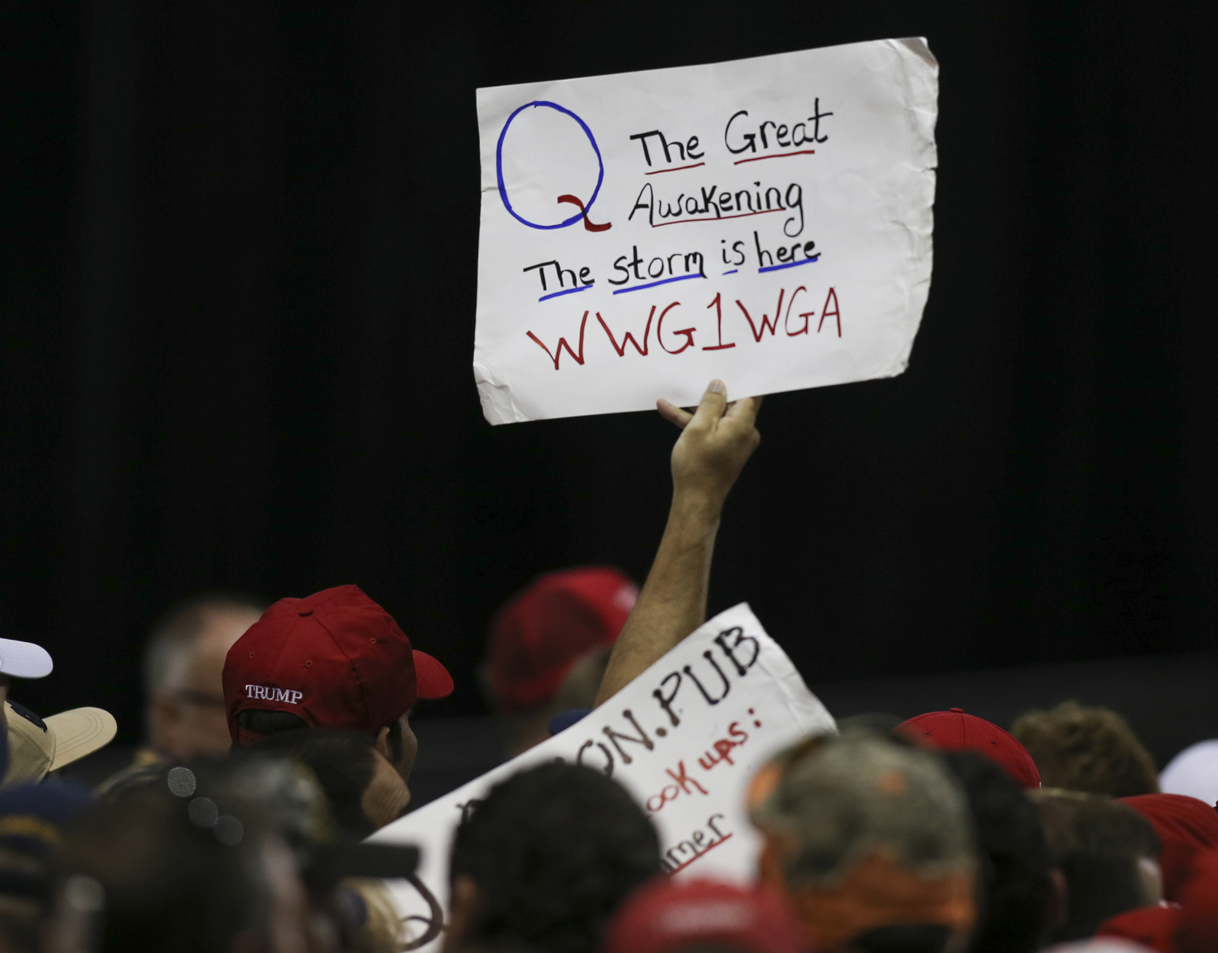 "A QAnon supporter in the crowd at a Trump rally holds a sign that reads, ""Q The great awakening. The storm is here WWG1WGA."""