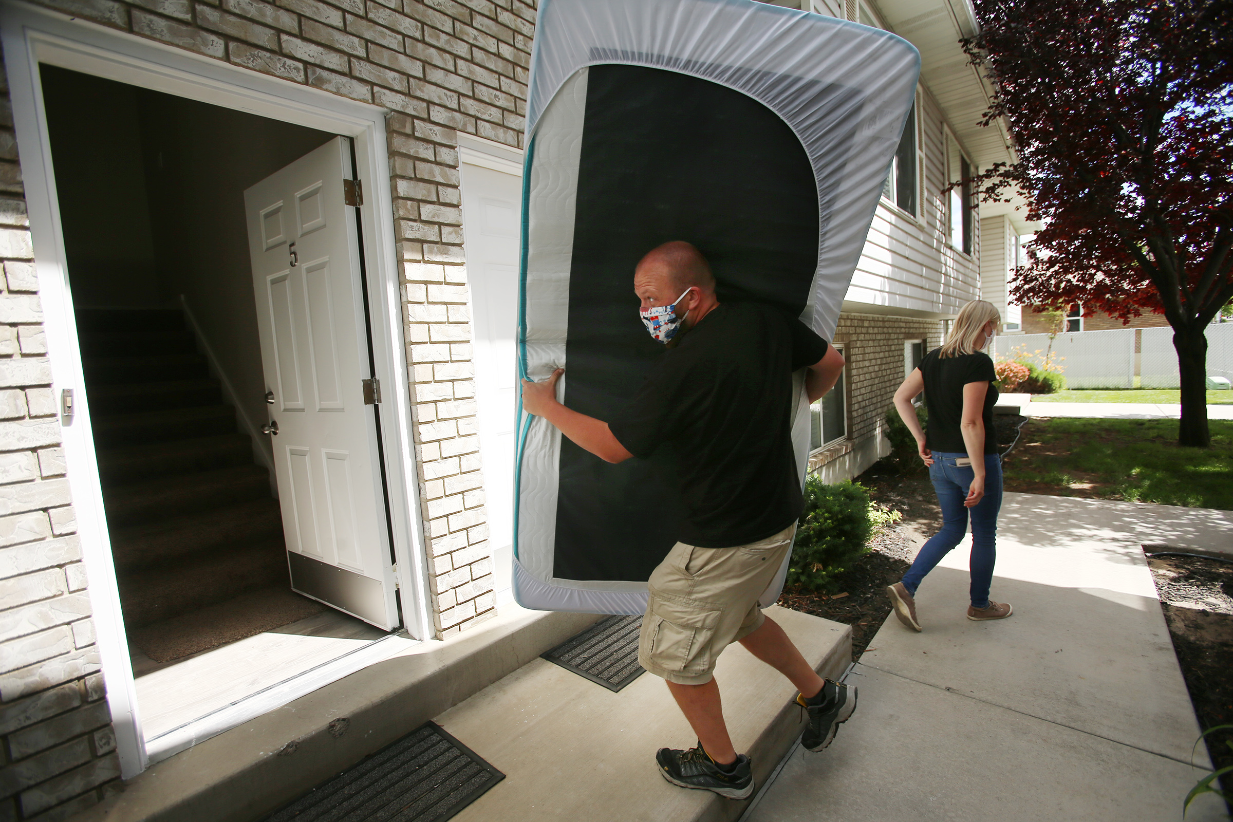 Matthew Tiemann carries a mattress into his condo in Provo as he and his wife, Courtney, unload their belongings on Tuesday, June 30, 2020. The couple had planned to go on a cruise and then COVID-19 happened and their plans changed.
