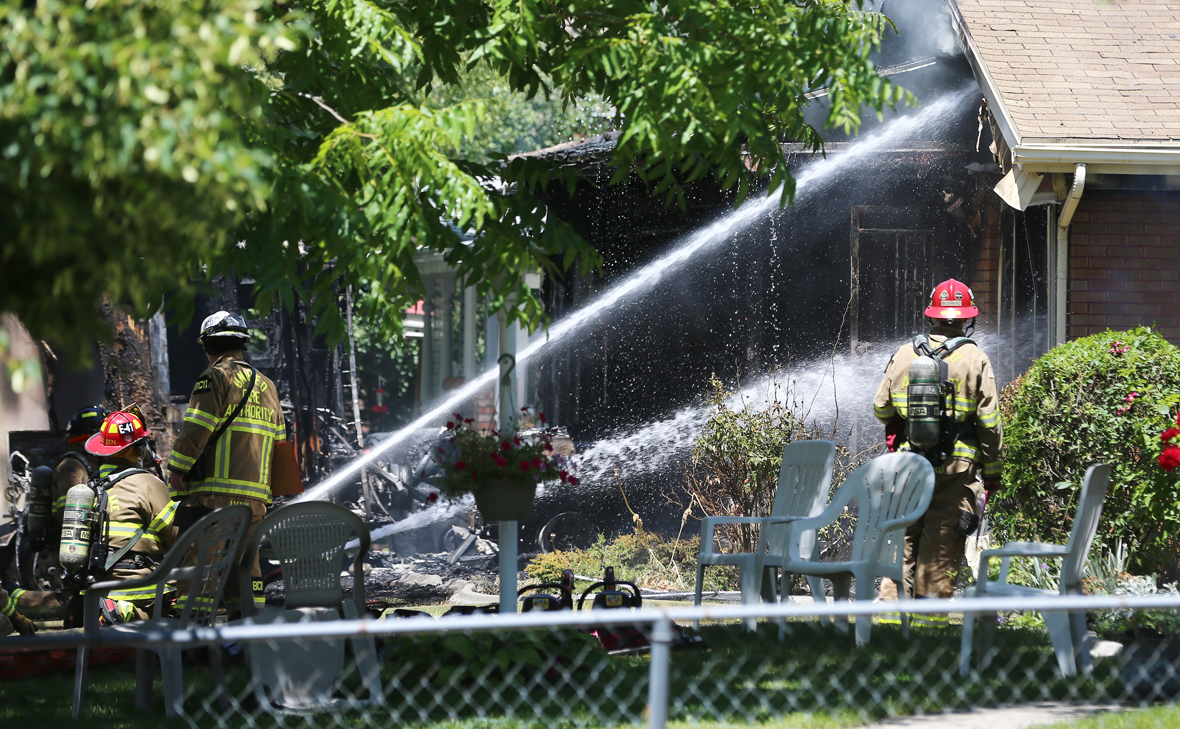 Unified Fire Authority firefighters spray water into a home as they fight a fire at 3381 S. 3170 East in Millecreek on Sunday, July 5, 2020.