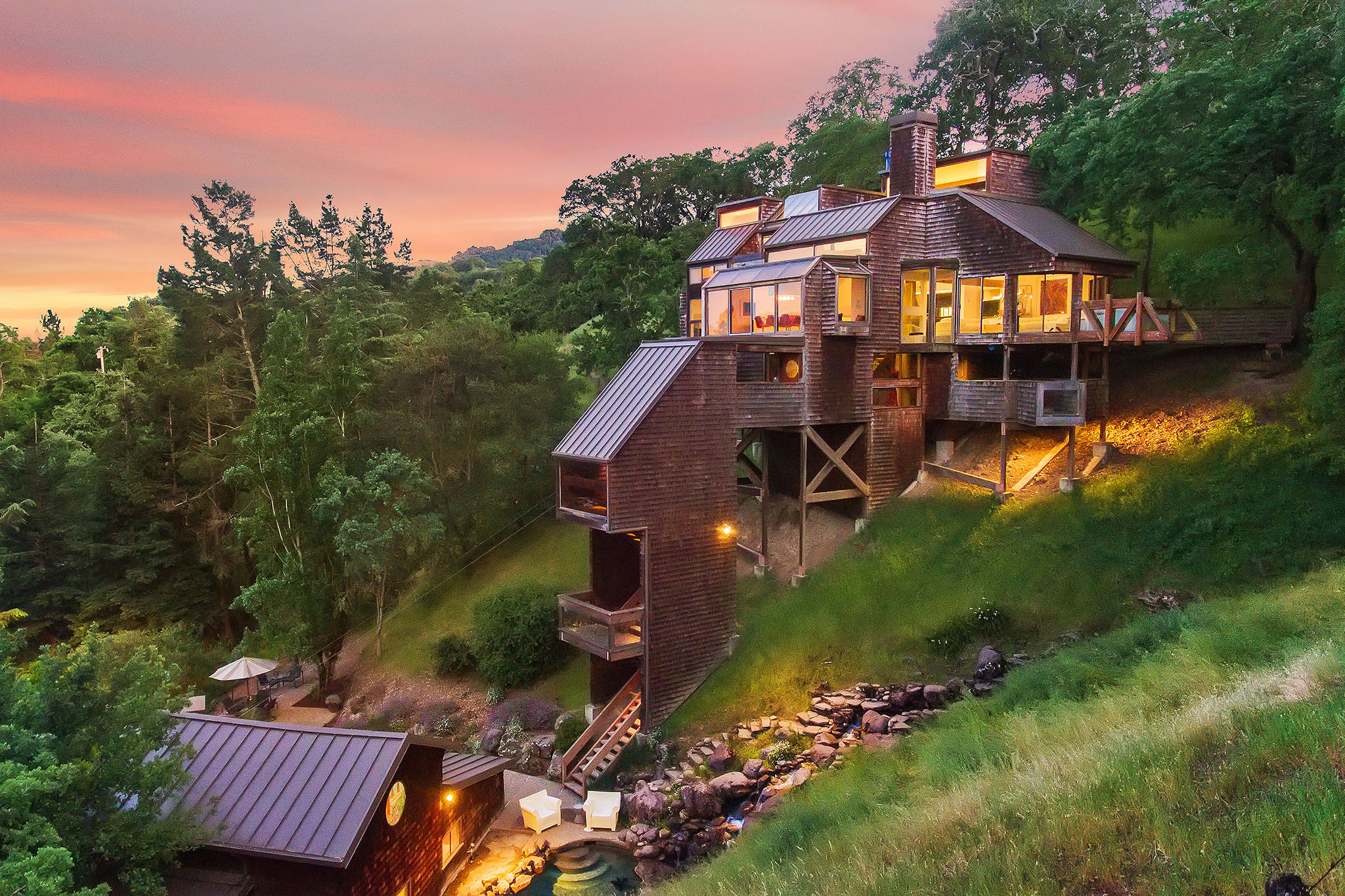 A hillside wooden house at dusk.