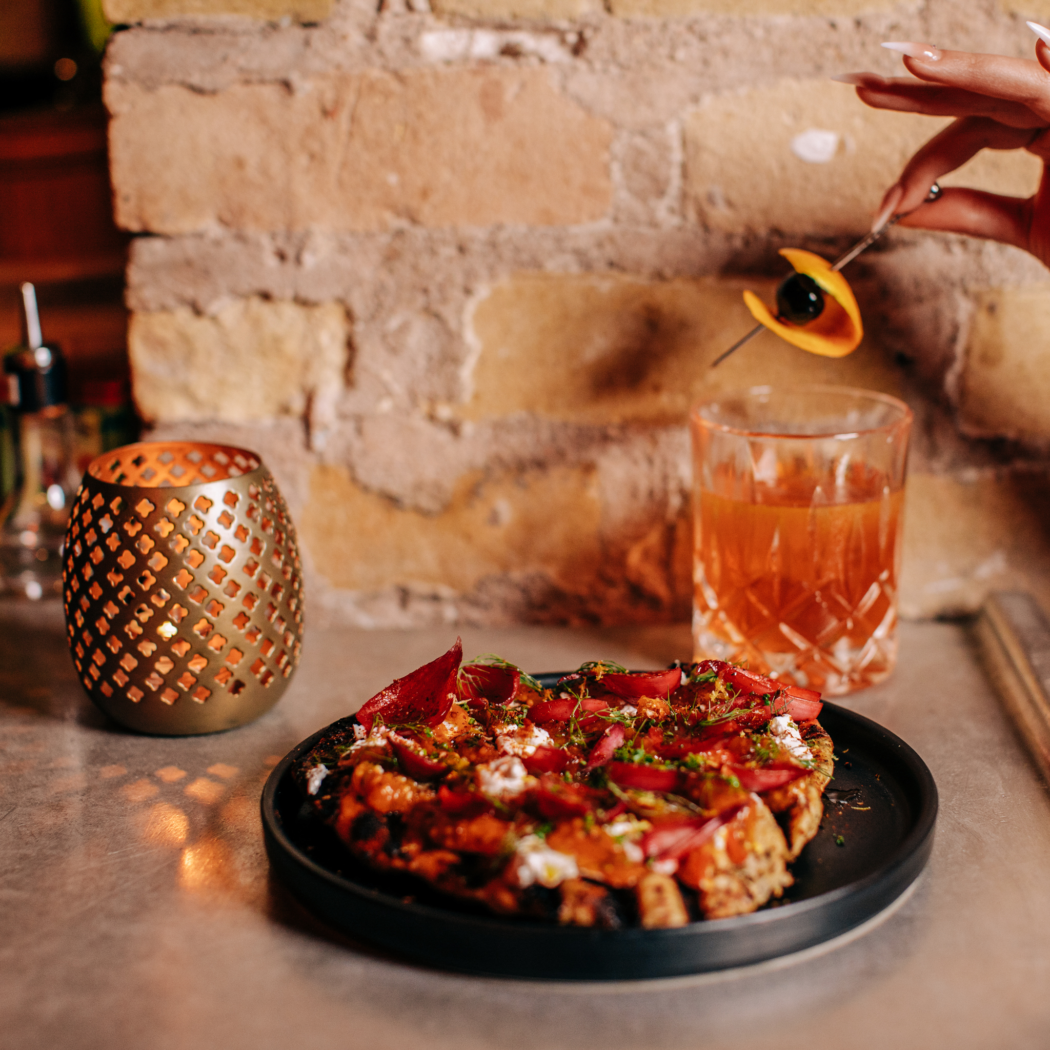 Flatbread with labneh, an orange cocktail, and a gold candleholder in front of a brick wall
