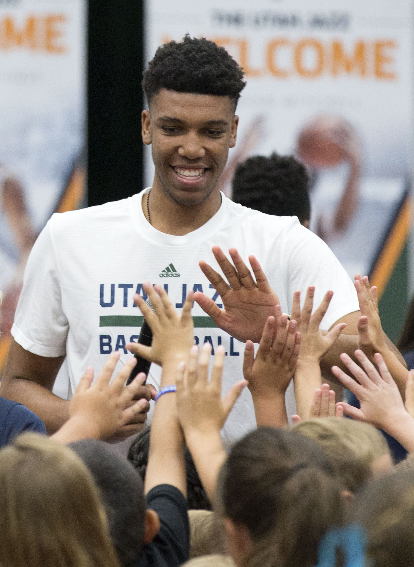 """Utah Jazz draft pick Tony Bradley is surrounded by students during a """"Welcome to Utah"""" assembly at South Jordan Elementary School on Thursday, June 29, 2017. Bradley joined fellow draft picks Nigel Williams-Goss and Donovan Mitchell at the assembly, where they read to more than 700 students, answered questions and stressed the importance of a good education."""