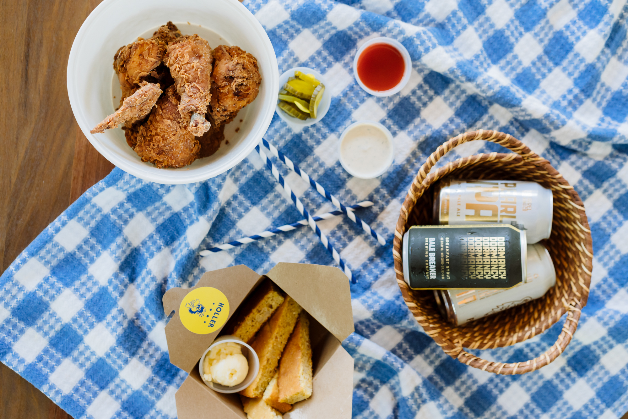 A bowl of fried chicken from Holler sits on a blue-and-white-checkered tablecloth, next to sticks of cornbread and a wicker basket full of canned beer