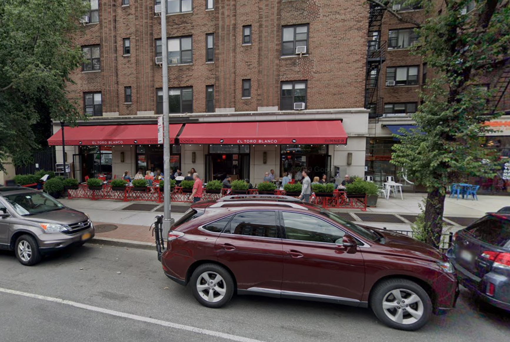 A streeview image with a car parked on the street and a restaurant with a red awning in the background.