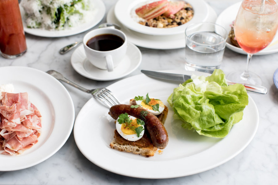 A plate of sausage and eggs, with a variety of sides and a cup of coffee at The Whale Wins