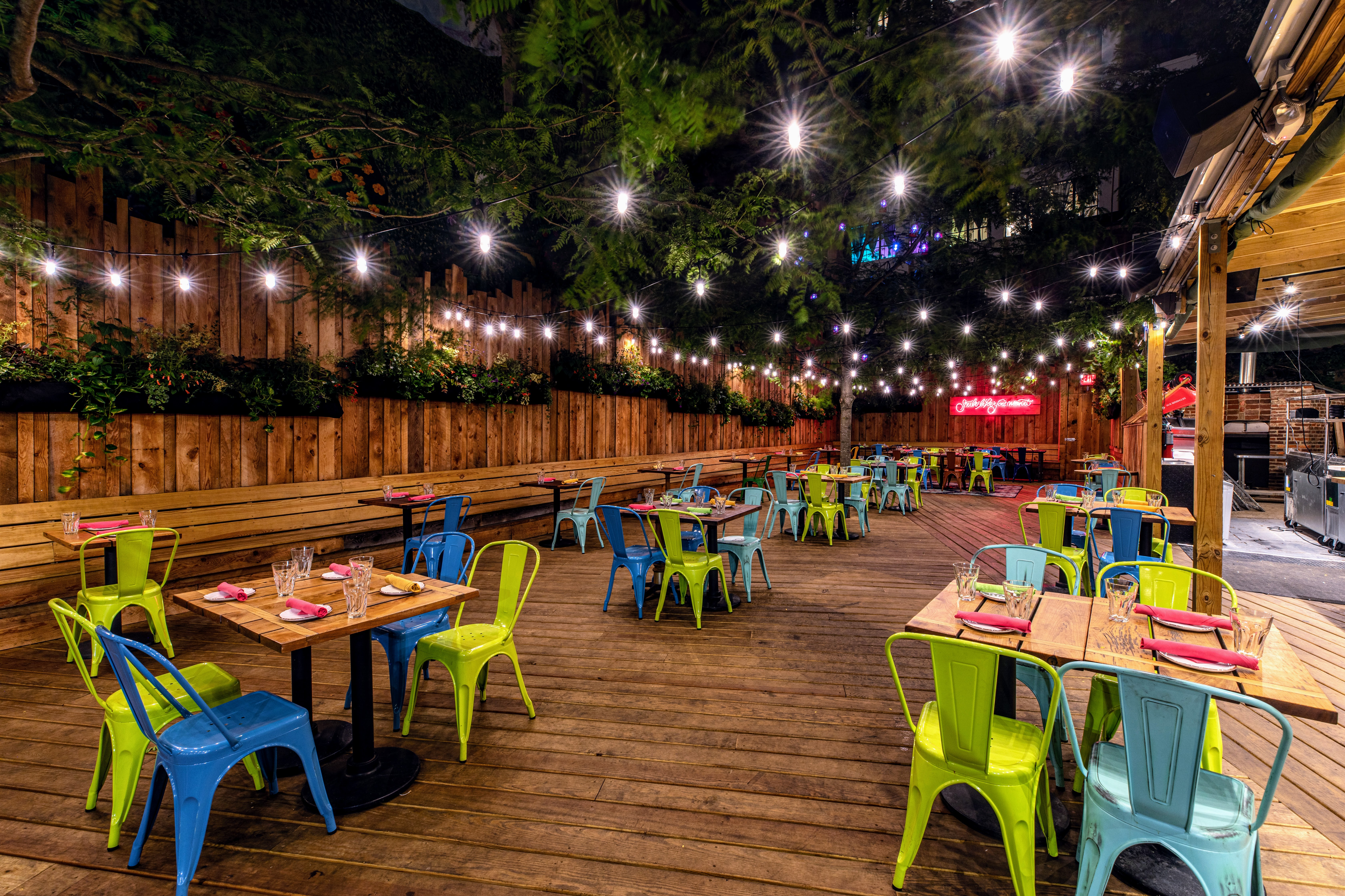 outdoor restaurant at night with string lights, colorful chairs and trees