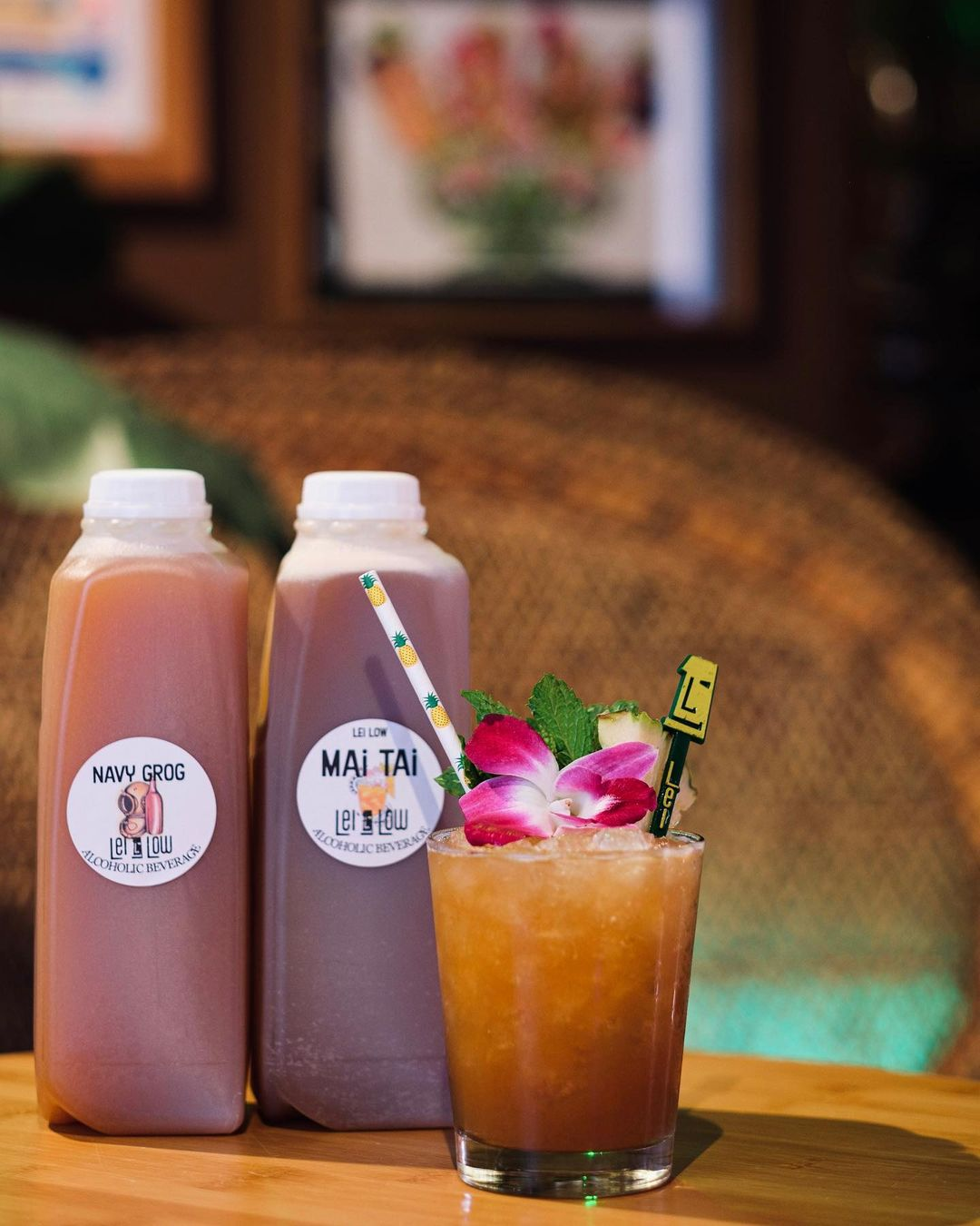 a mai tai next to two plastic cartons of takeout booze