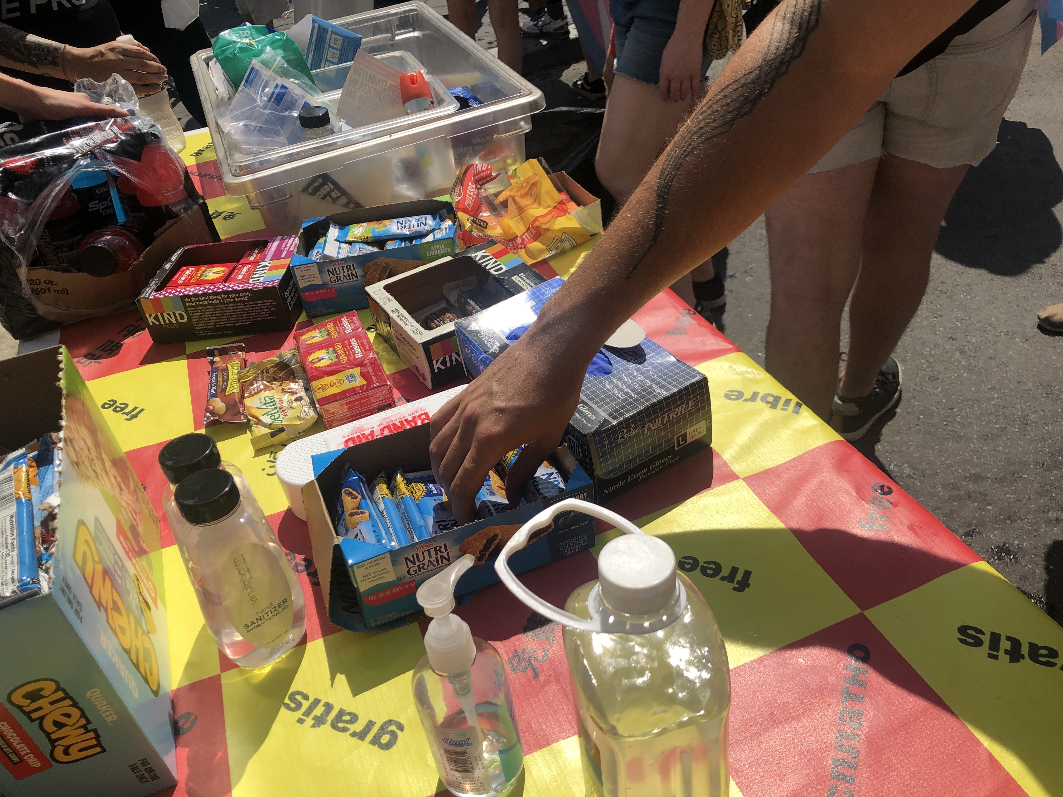 A hand reaching for a granola bar on a table surrounded by other snacks
