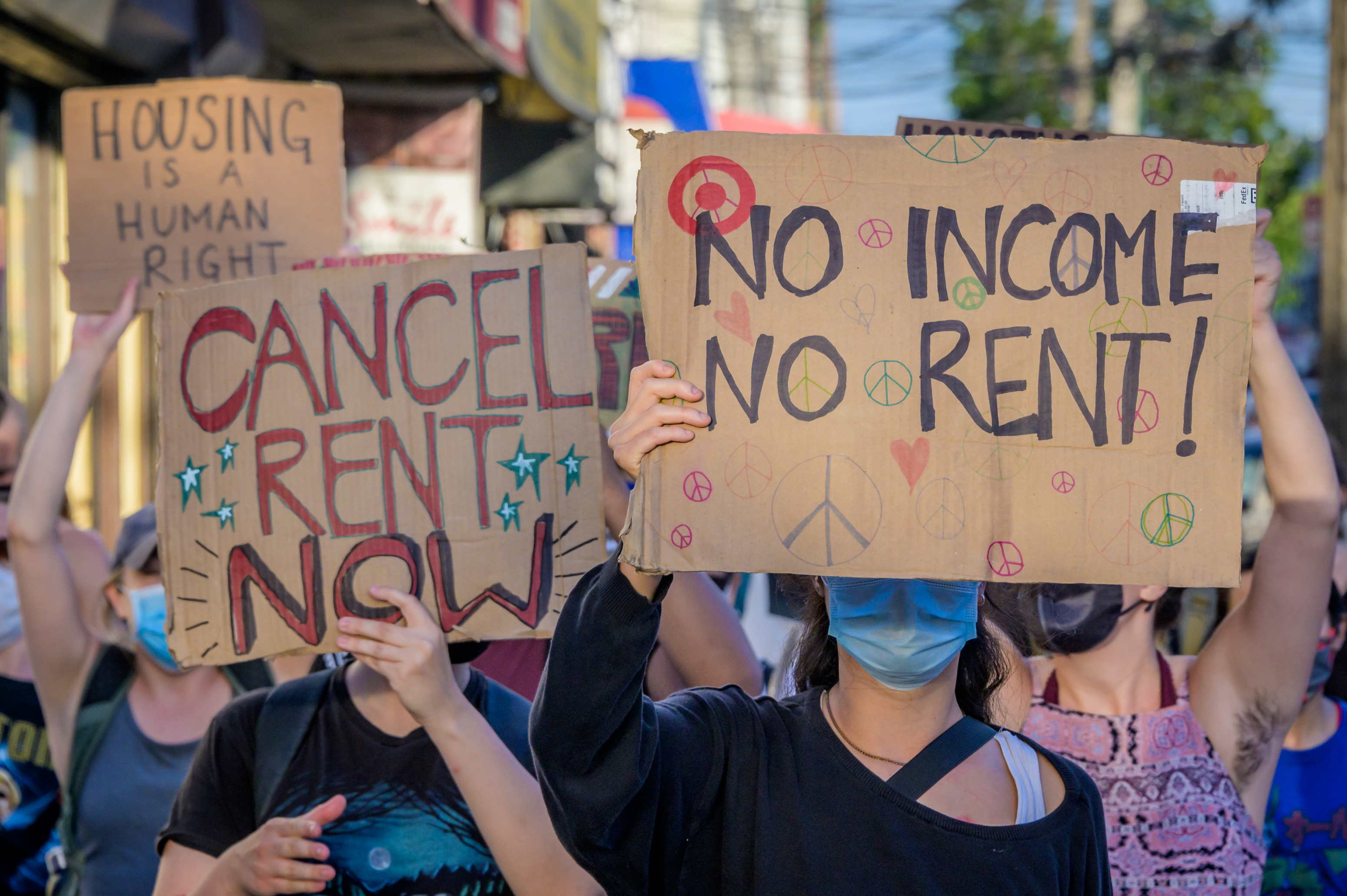 """New Yorkers carrying signs painted with """"Cancel Rent Now"""" and """"No Income No Relief"""" during a Brooklyn protest."""