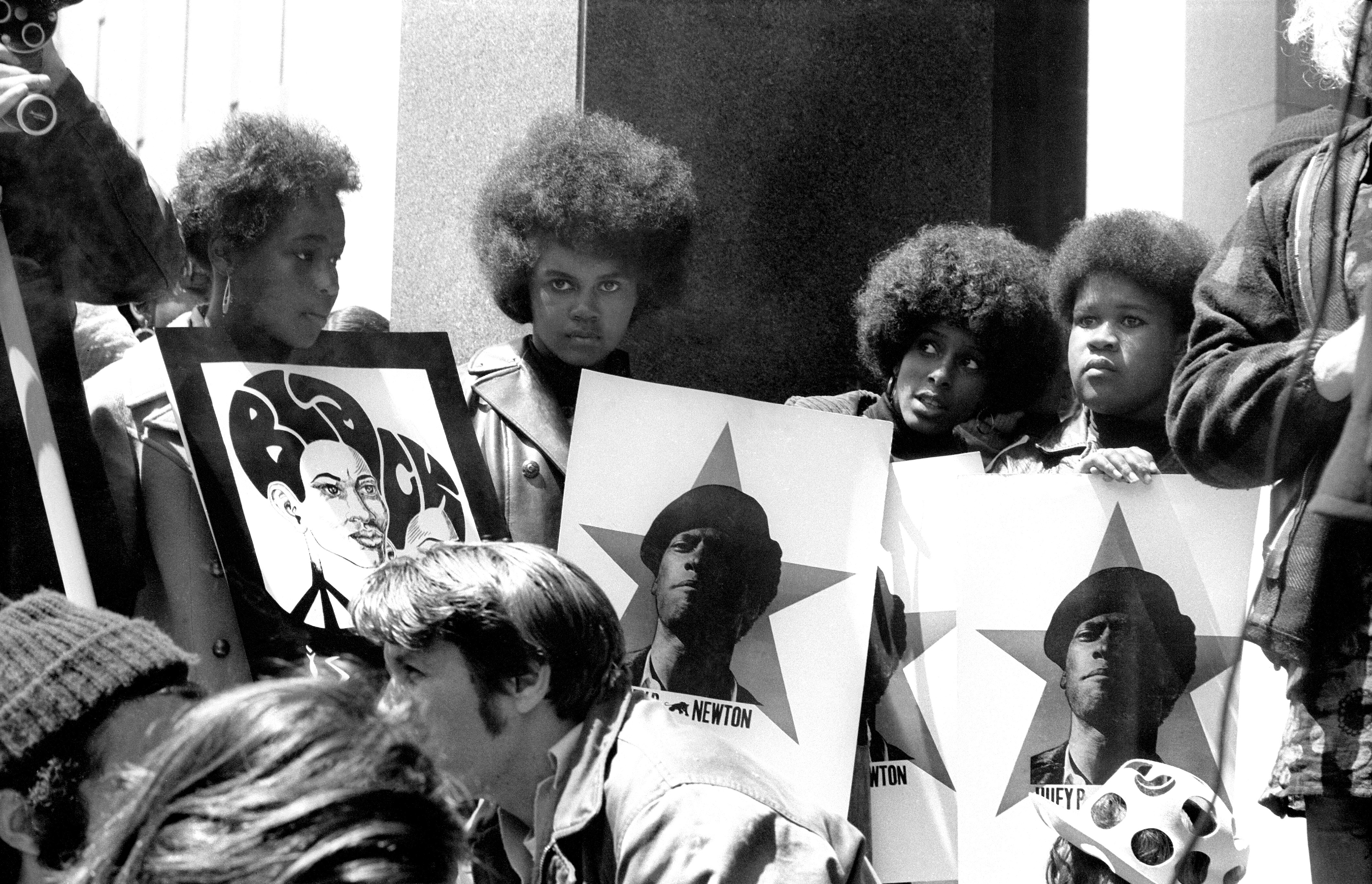 A group of Black women hold signs showing a picture of Black Panthers Party co-founder Huey P. Newton at a protest in 1969.