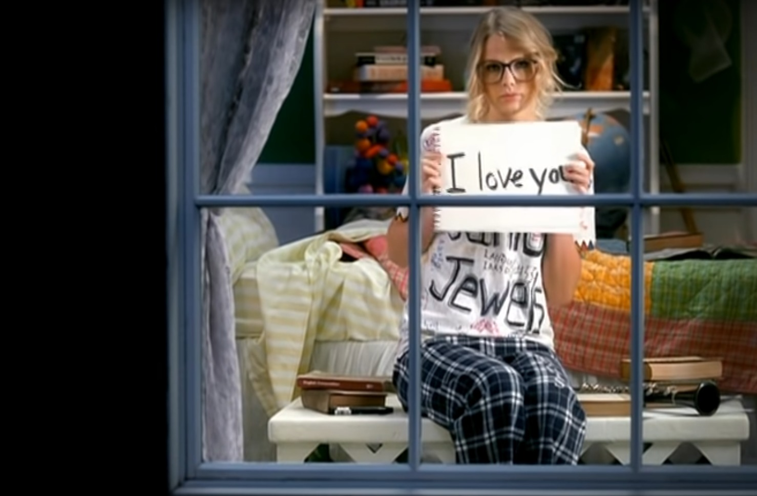 """Taylor Swift holding up a sign that reads """"I Love You"""" in her music video You Belong With Me"""