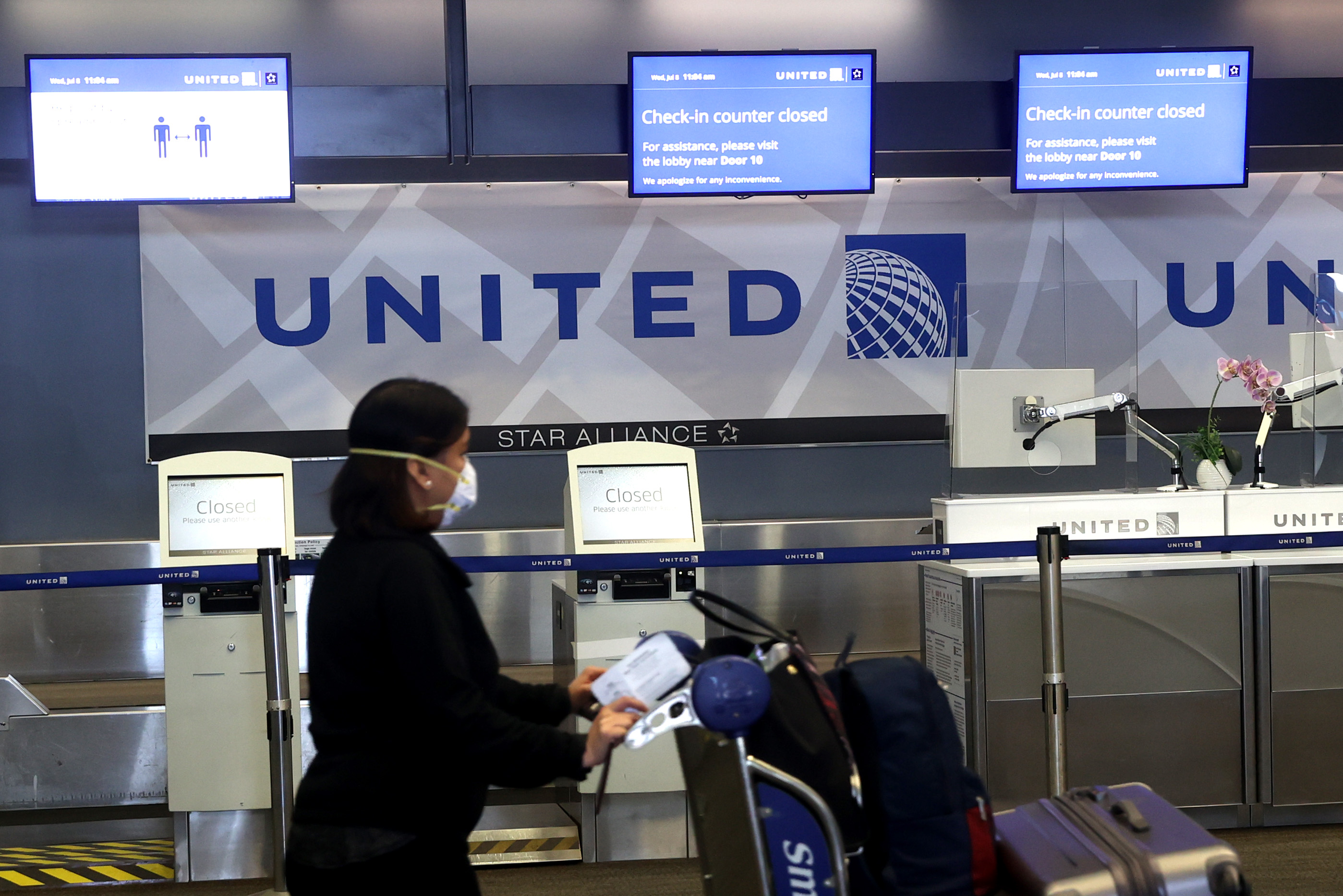 A United Airlines passenger pushes a luggage cart past a closed check-in kiosk in San Francisco on Wednesday.