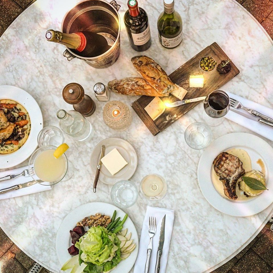 A table with three settings of food, bread, butter, and wine