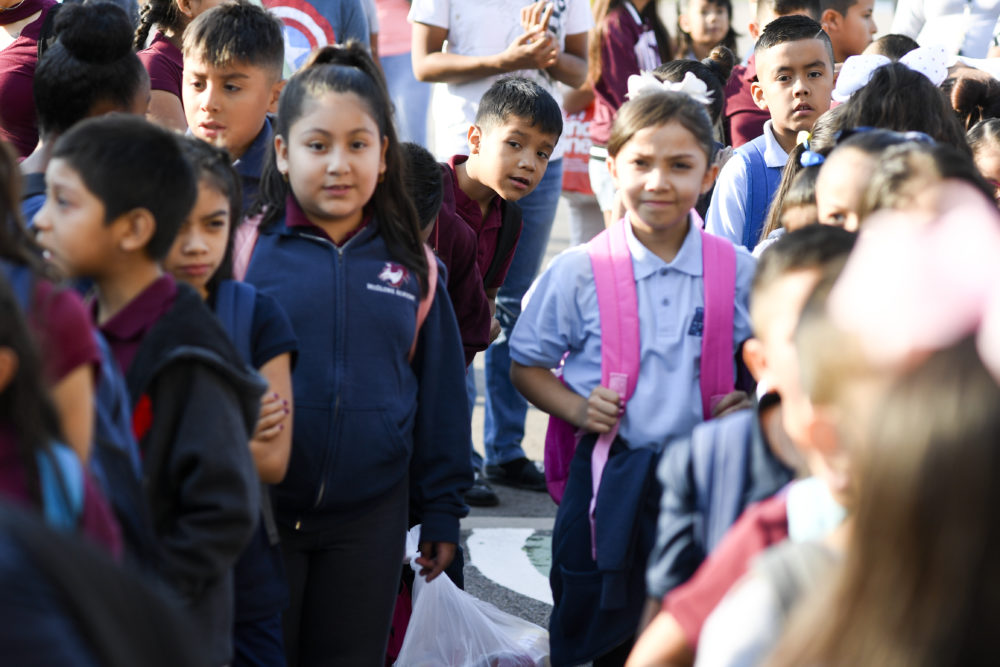 Angel Trigueros-Martinez pokes his head from the back of the line as students wait to enter the building on the first day of school at McGlone Academy on Wednesday. (Photo by AAron Ontiveroz/The Denver Post)