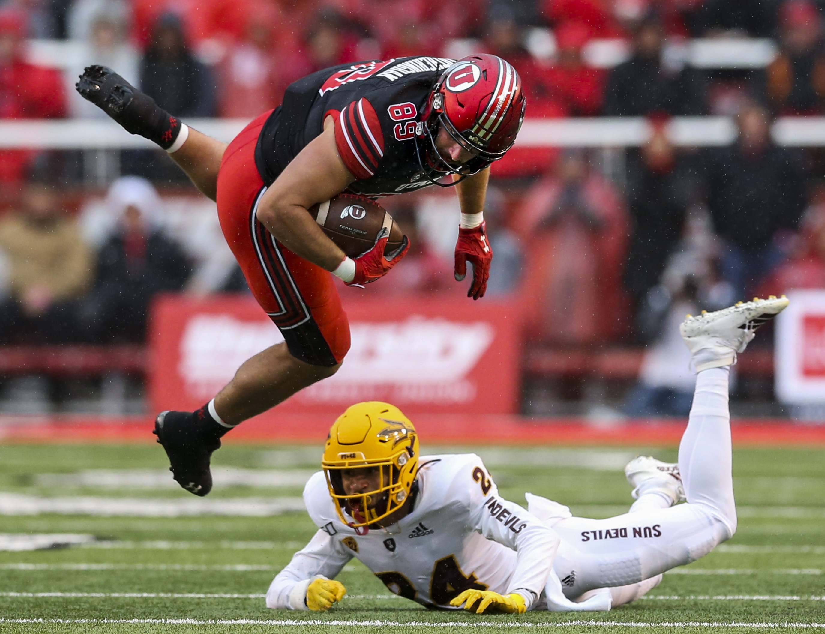 Utah Utes tight end Cole Fotheringham (89) is flipped through the air by Arizona State Sun Devils defensive back Chase Lucas (24) during the first half of an NCAA football game at Rice-Eccles Stadium in Salt Lake City on Saturday, Oct. 19, 2019.