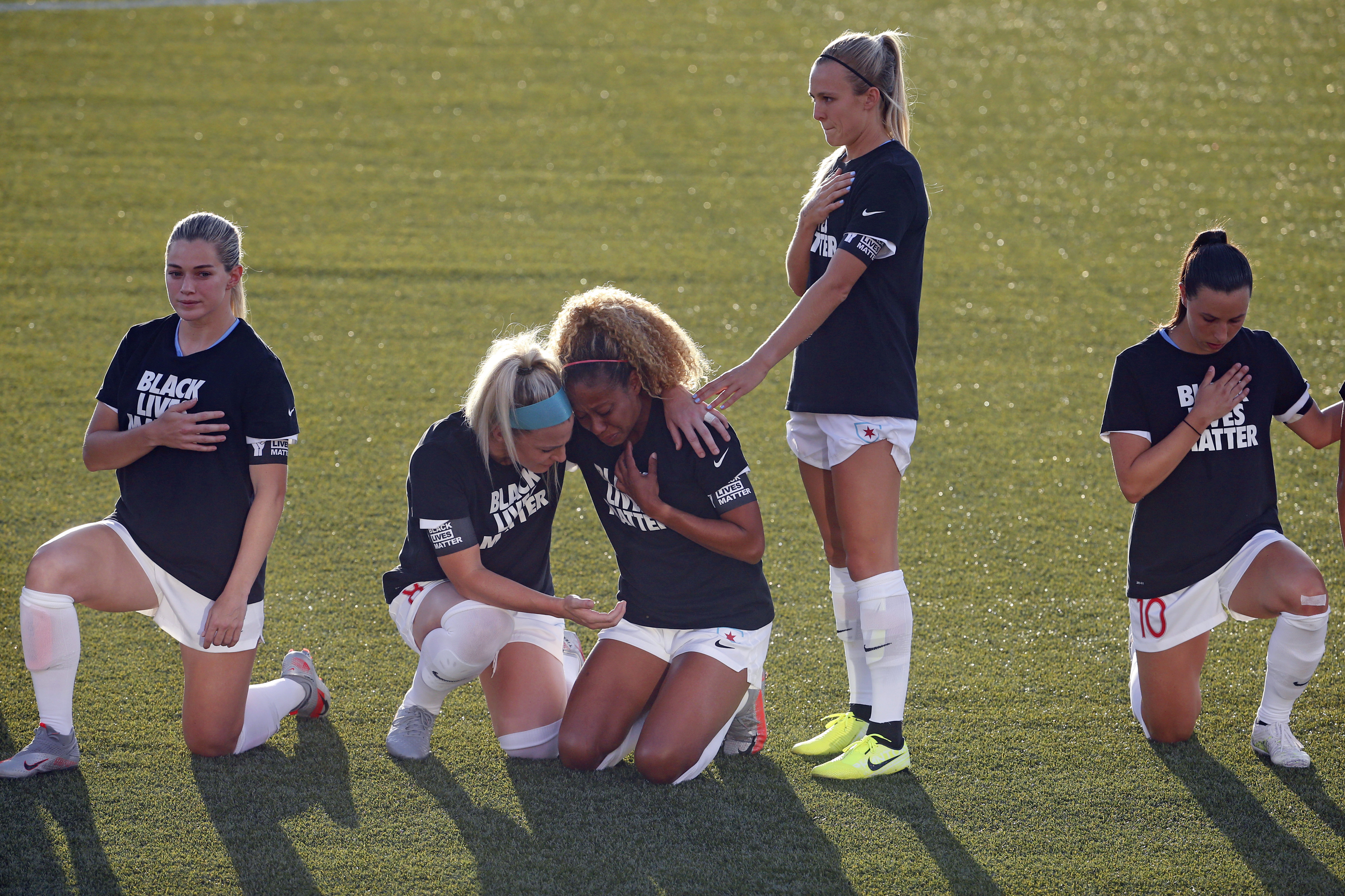 FILE - In this June 27, 2020, file phohto, Chicago Red Stars' Julie Ertz, second from left, holds Casey Short, center, while other players for the team kneel during the national anthem before an NWSL Challenge Cup soccer match against the Washington Spirit at Zions Bank Stadium in Herriman, Utah. The National Women's Soccer League revised its anthem policy after most players knelt during the anthem before season-opening games last weekend at the Challenge Cup. (AP Photo/Rick Bowmer, File) ORG XMIT: NY158