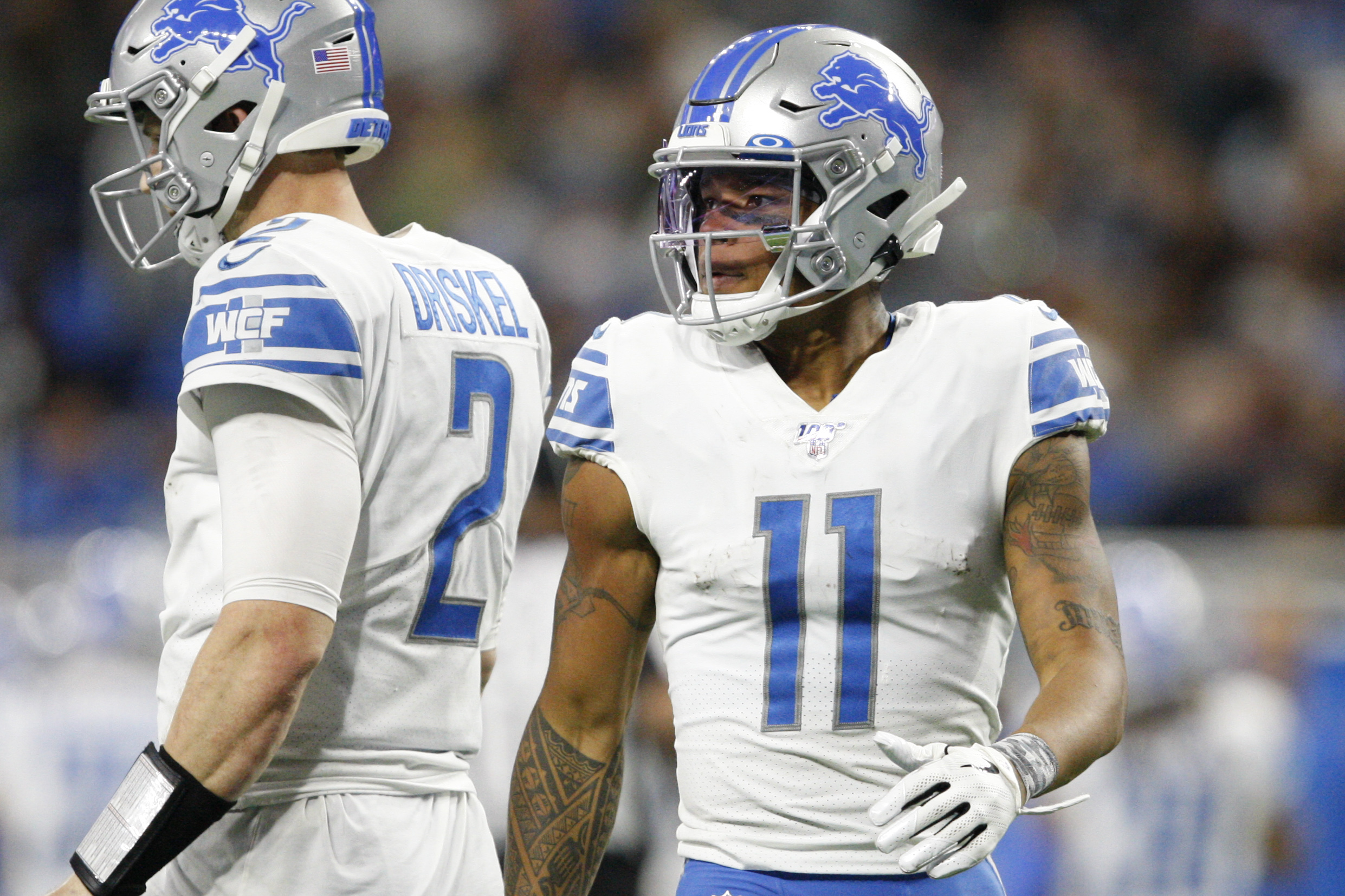 Detroit Lions wide receiver Marvin Jones walks behind quarterback Jeff Driskel before a play during the fourth quarter against the Dallas Cowboys at Ford Field.