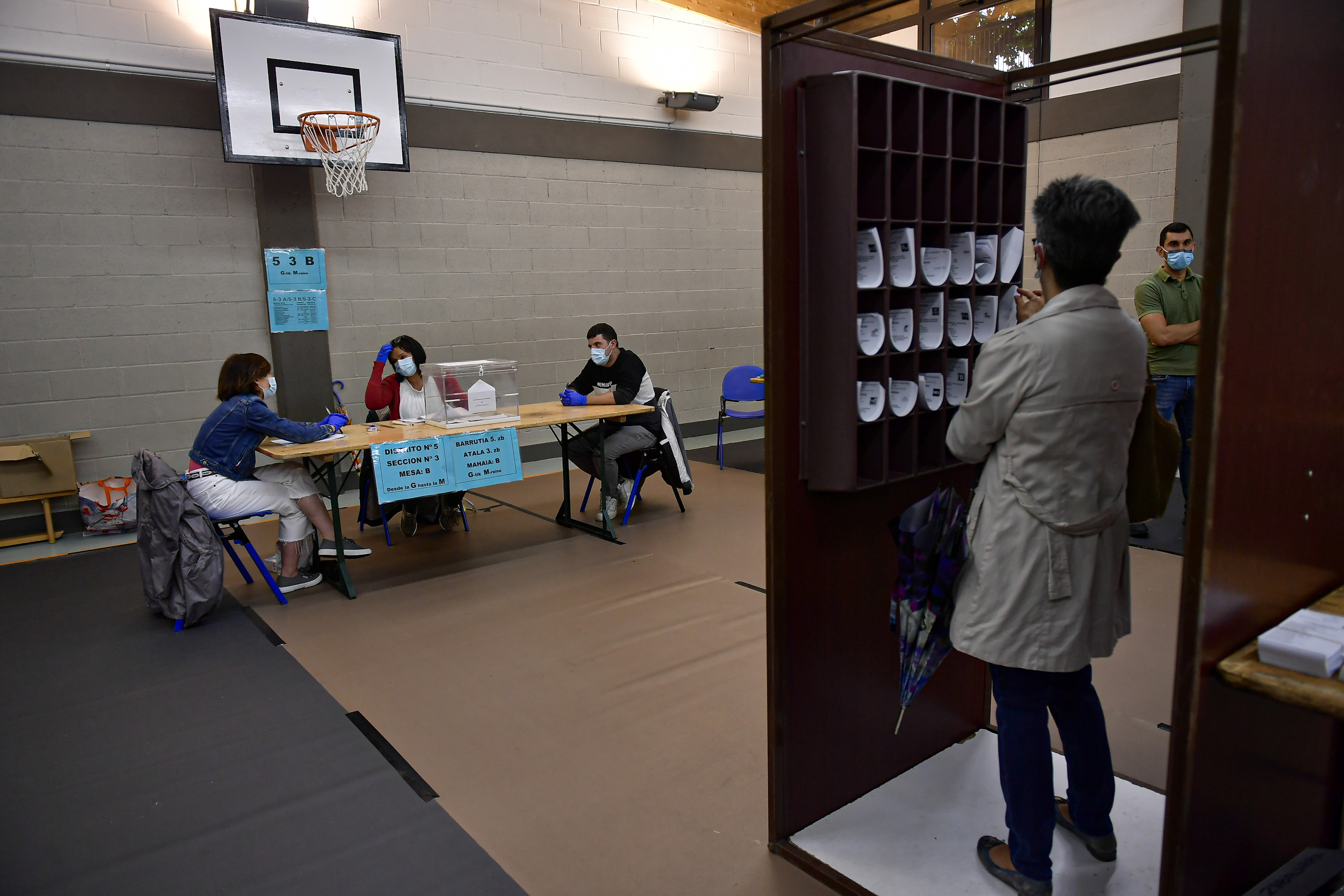 A woman prepares her vote while staff members of a polling station wear face masks to help curb the spread of the coronavirus during the Basque regional election in the village of Durango, northern Spain, Sunday, July 12, 2020. Basque authorities are displaying special rules and practices in the protection against the coronavirus.