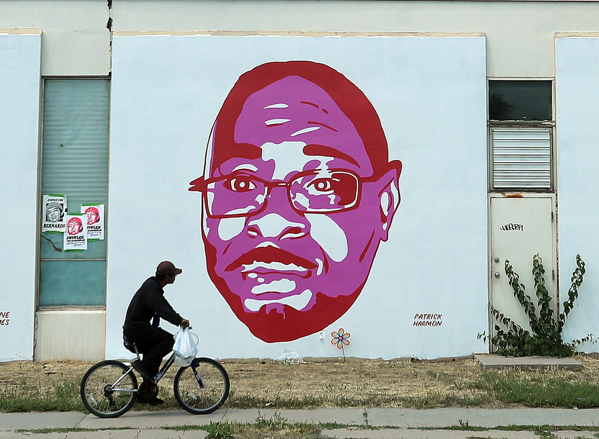 A bicyclist rides past a mural of Patrick Harmon, who was shot and killed by police, in Salt Lake City on Monday, July 13, 2020. A federal judge has dismissed a lawsuit from Harmon's family, rejecting their allegations of excessive force and racial discrimination.