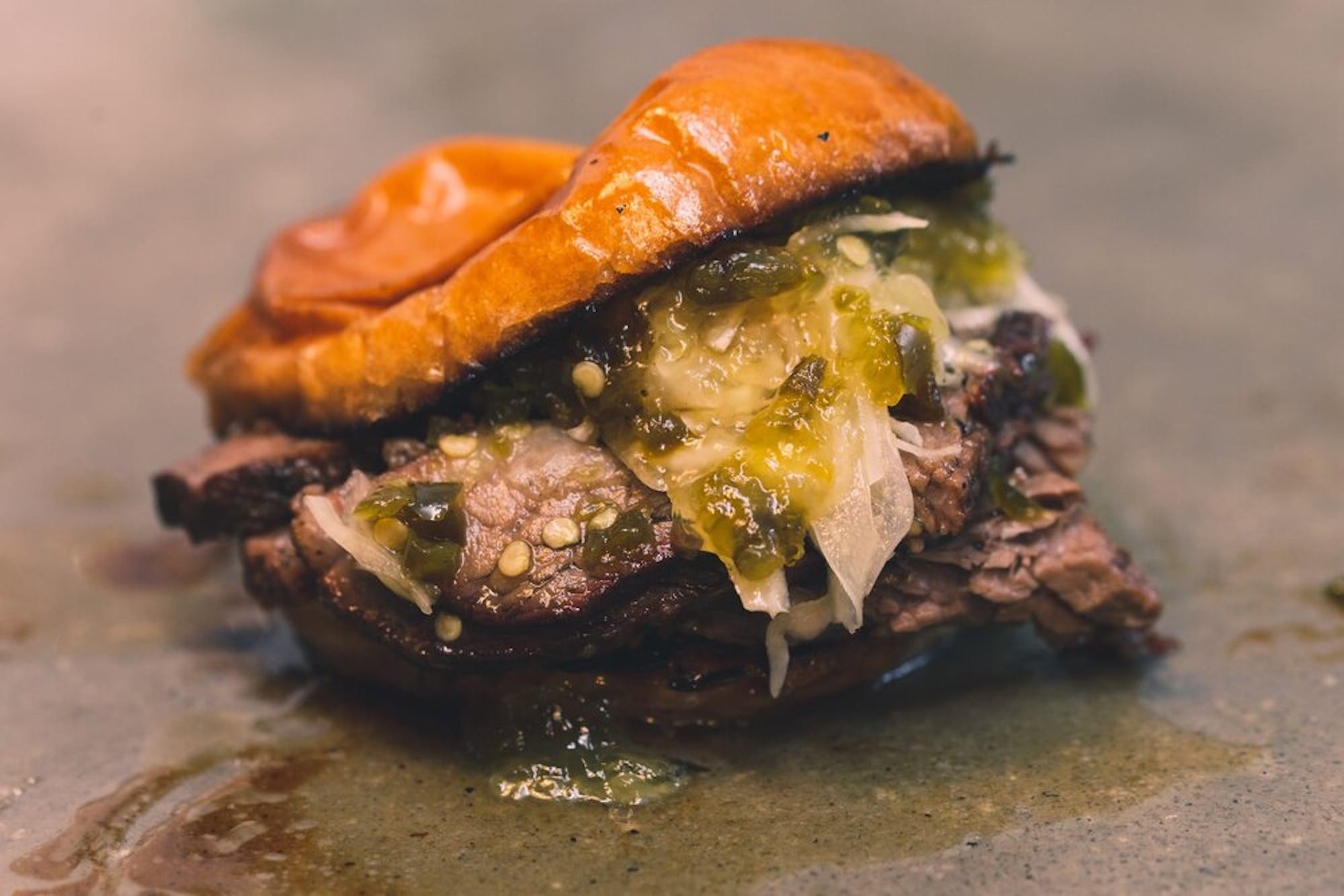 Takeaway barbecue brisket bun with meat, pickles, and cheese on a plancha grill