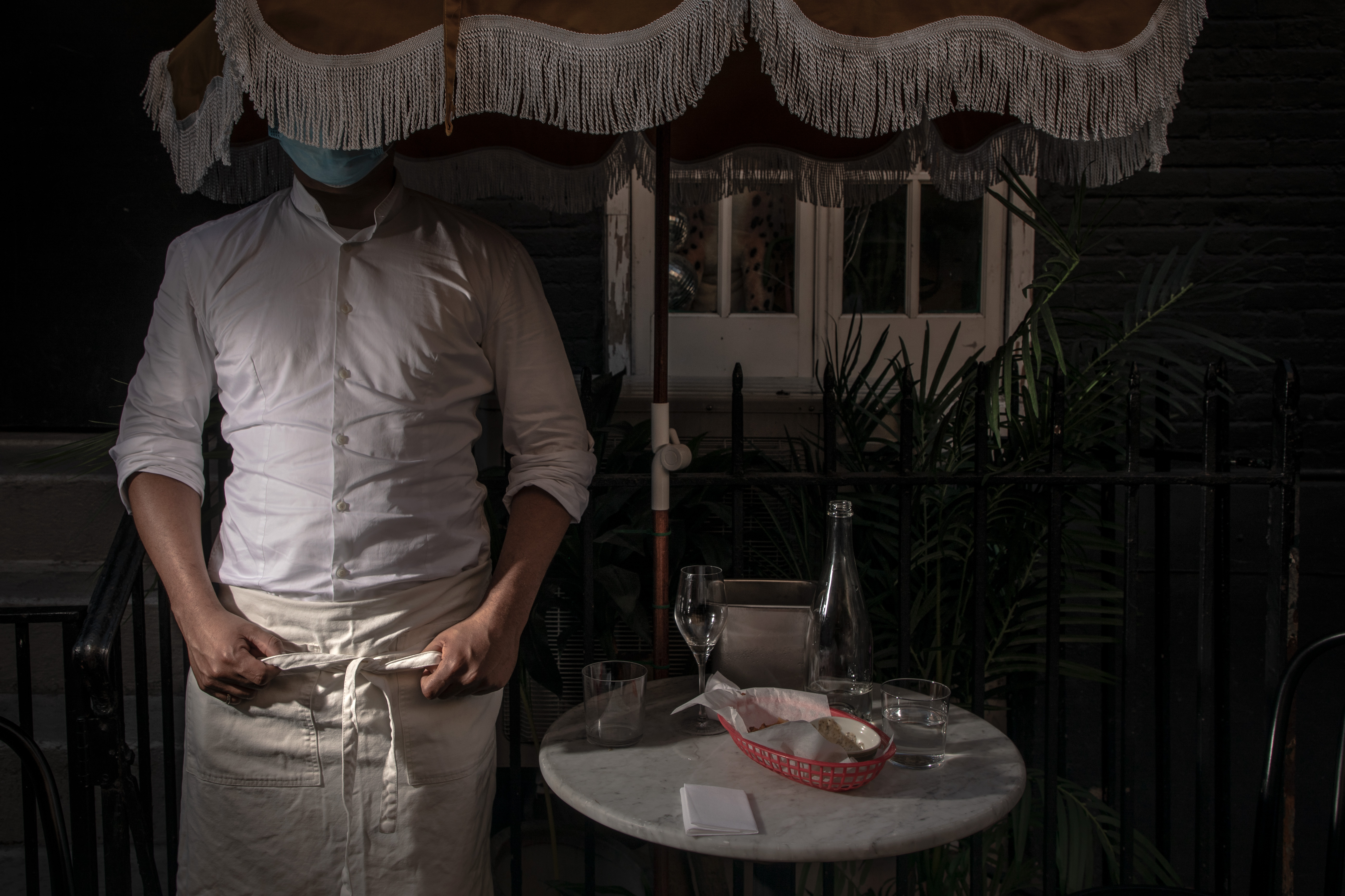 A man adjusts his apron standing next to a table with his face obscured by an umbrella.