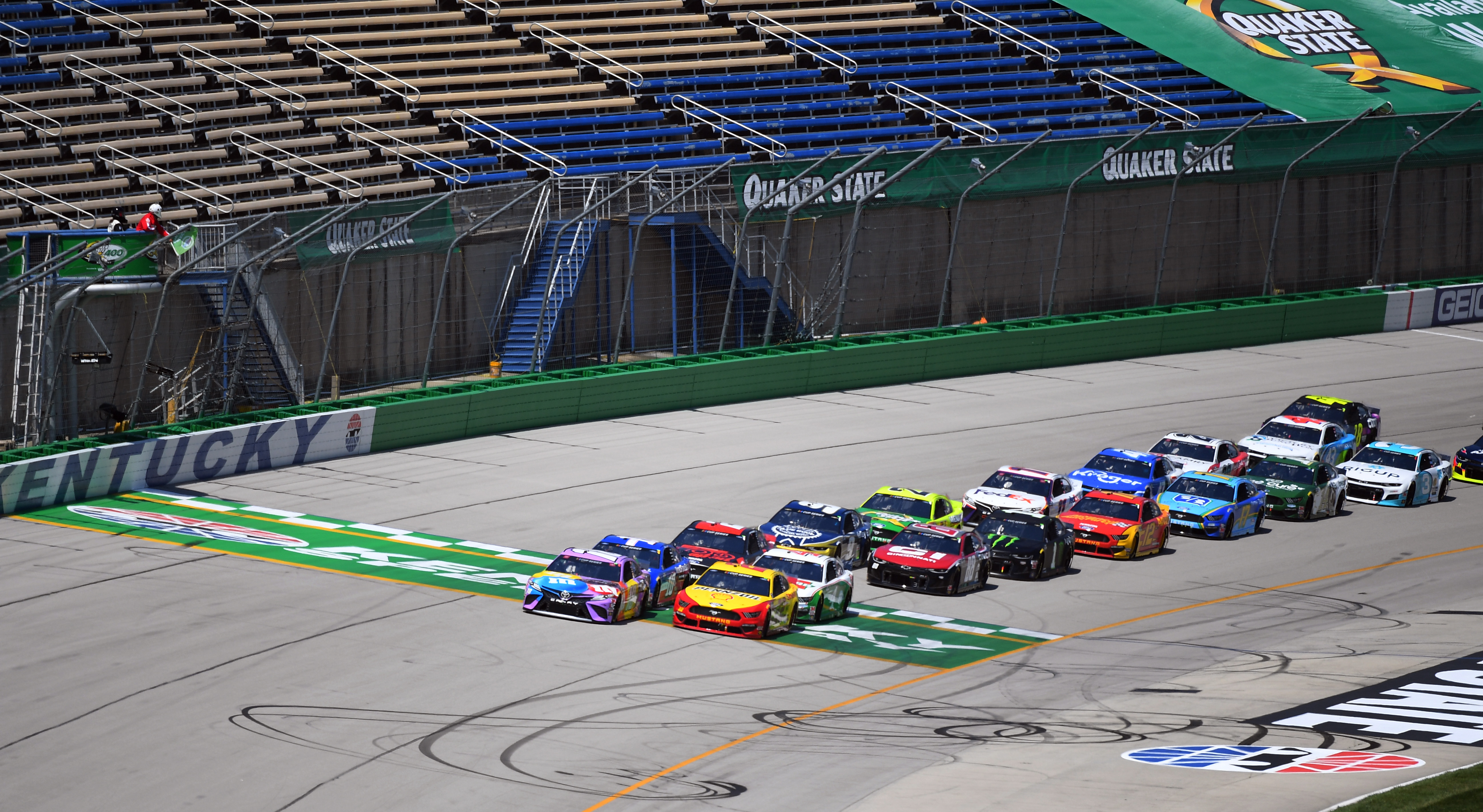 Monster Energy NASCAR Cup Series driver Kyle Busch and Monster Energy NASCAR Cup Series driver Joey Logano lead the field across the start finish line during the Quaker State 400 at Kentucky Speedway.