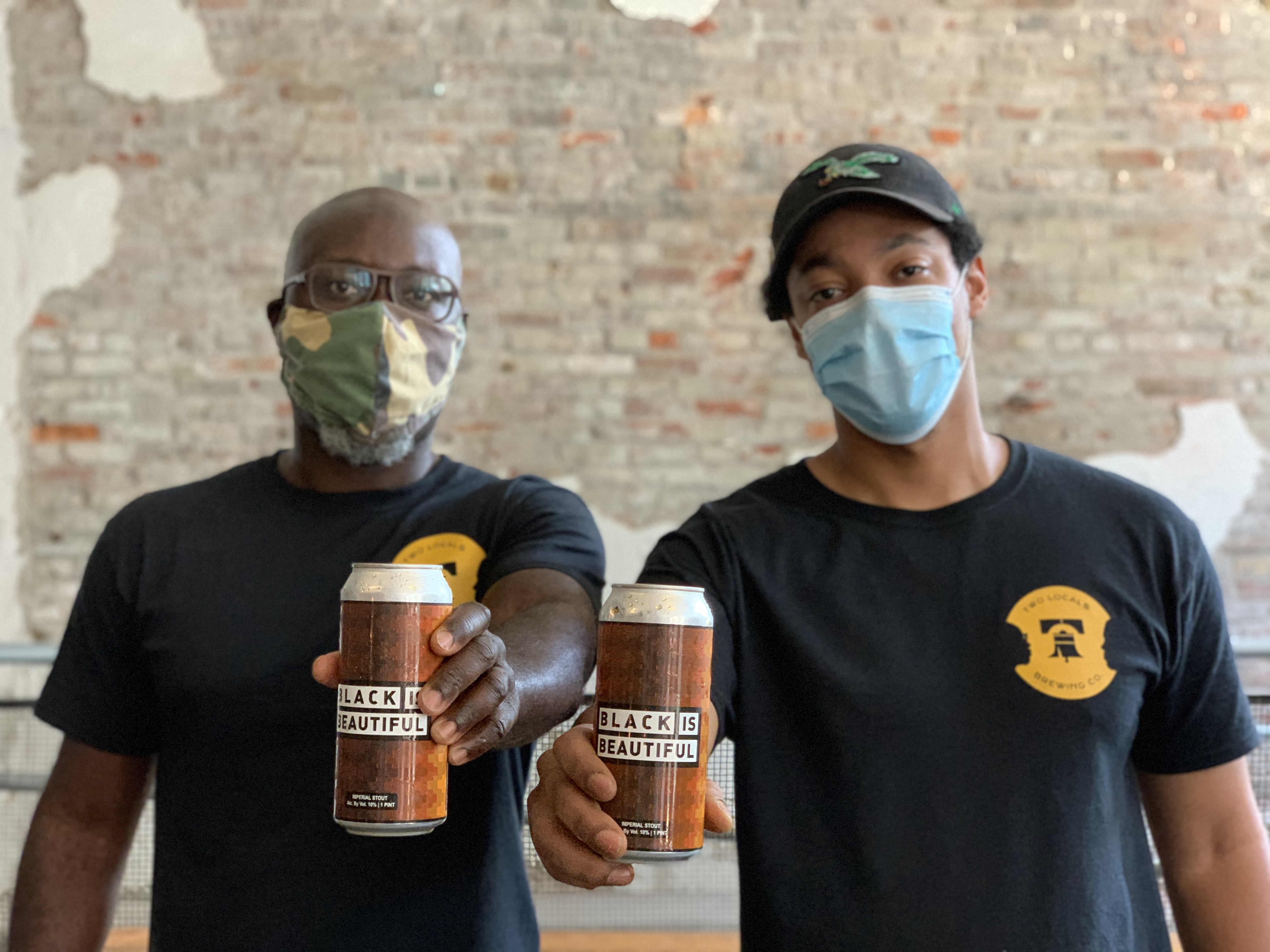 two men with pandemic face masks holding cans of beer