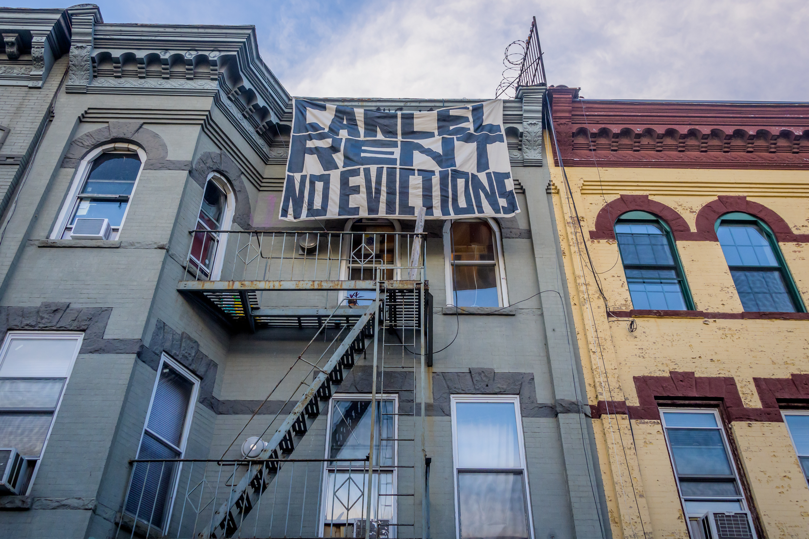 """A banner painted with """"Cancel Rent No Evictions"""" hangs off the facade of a blue, brick apartment building in Bushwick, Brooklyn."""