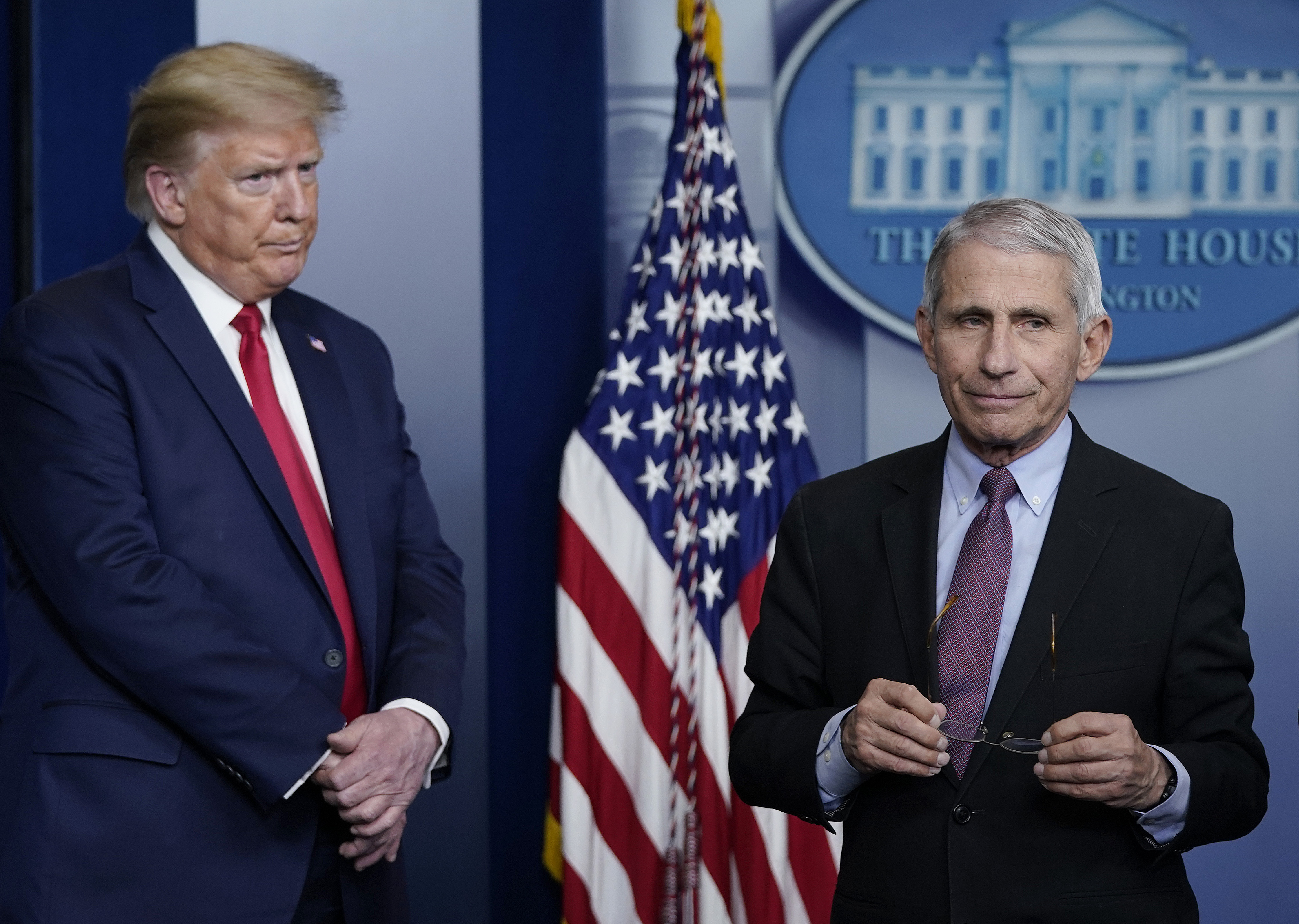 Donald Trump and Anthony Fauci stand on either side of an American flag on the White House press room stage in April 2020.