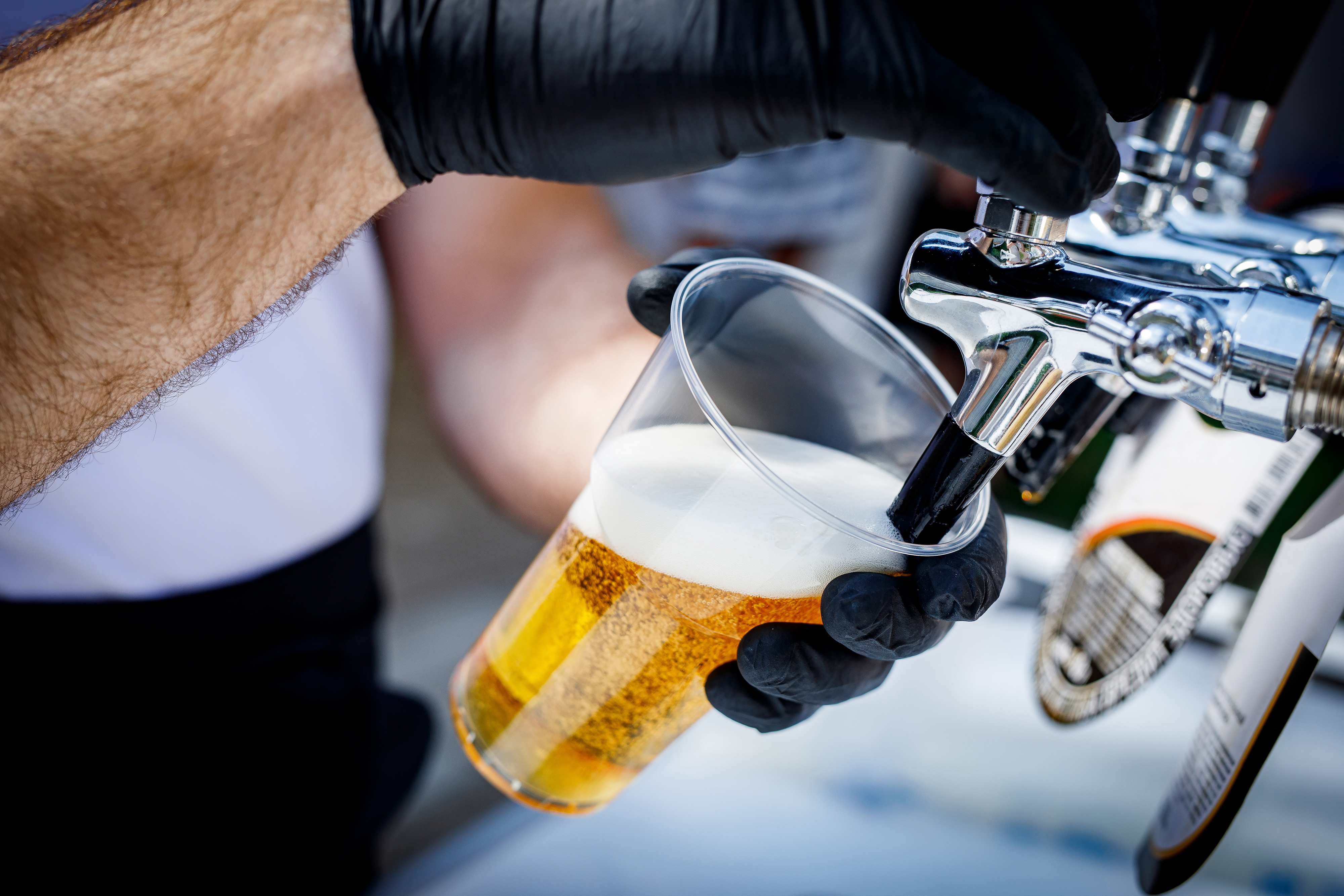 A bartender in black gloves pours beer into a disposable plastic glass.