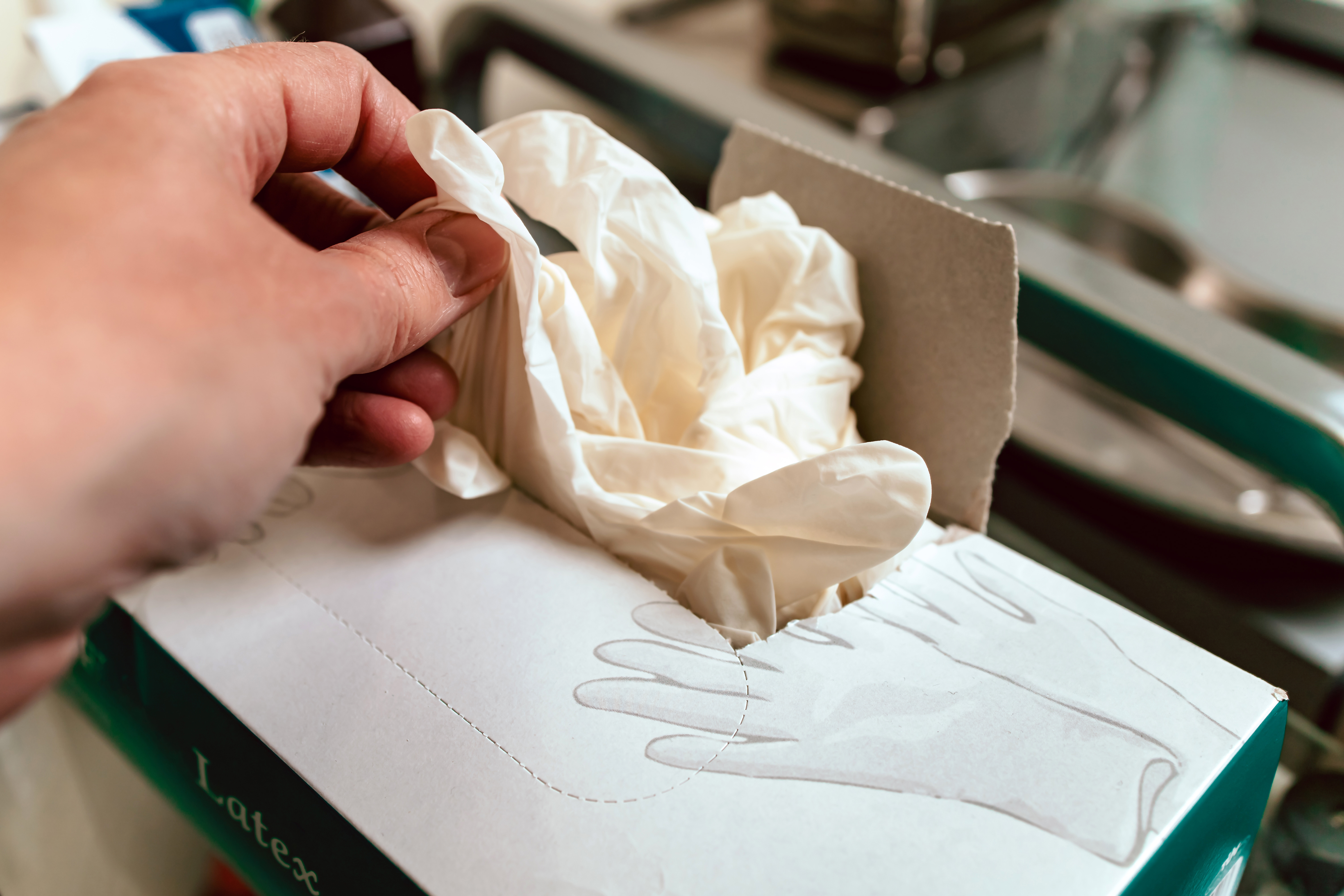 A hand takes a protective white latex glove from a box of gloves.