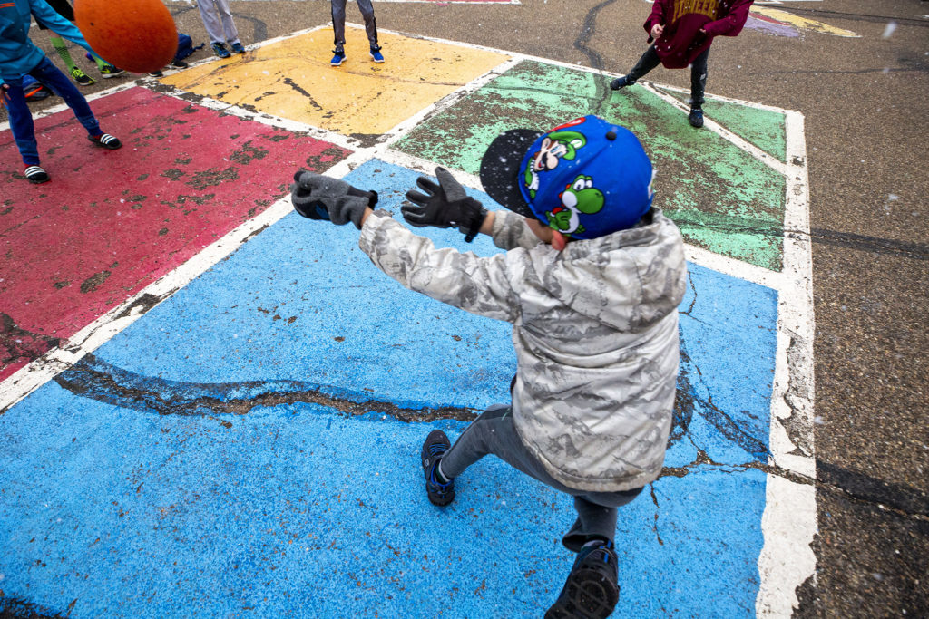 Kids play foursquare beneath light flurries before class begins at Carson Elementary, March 13, 2020.