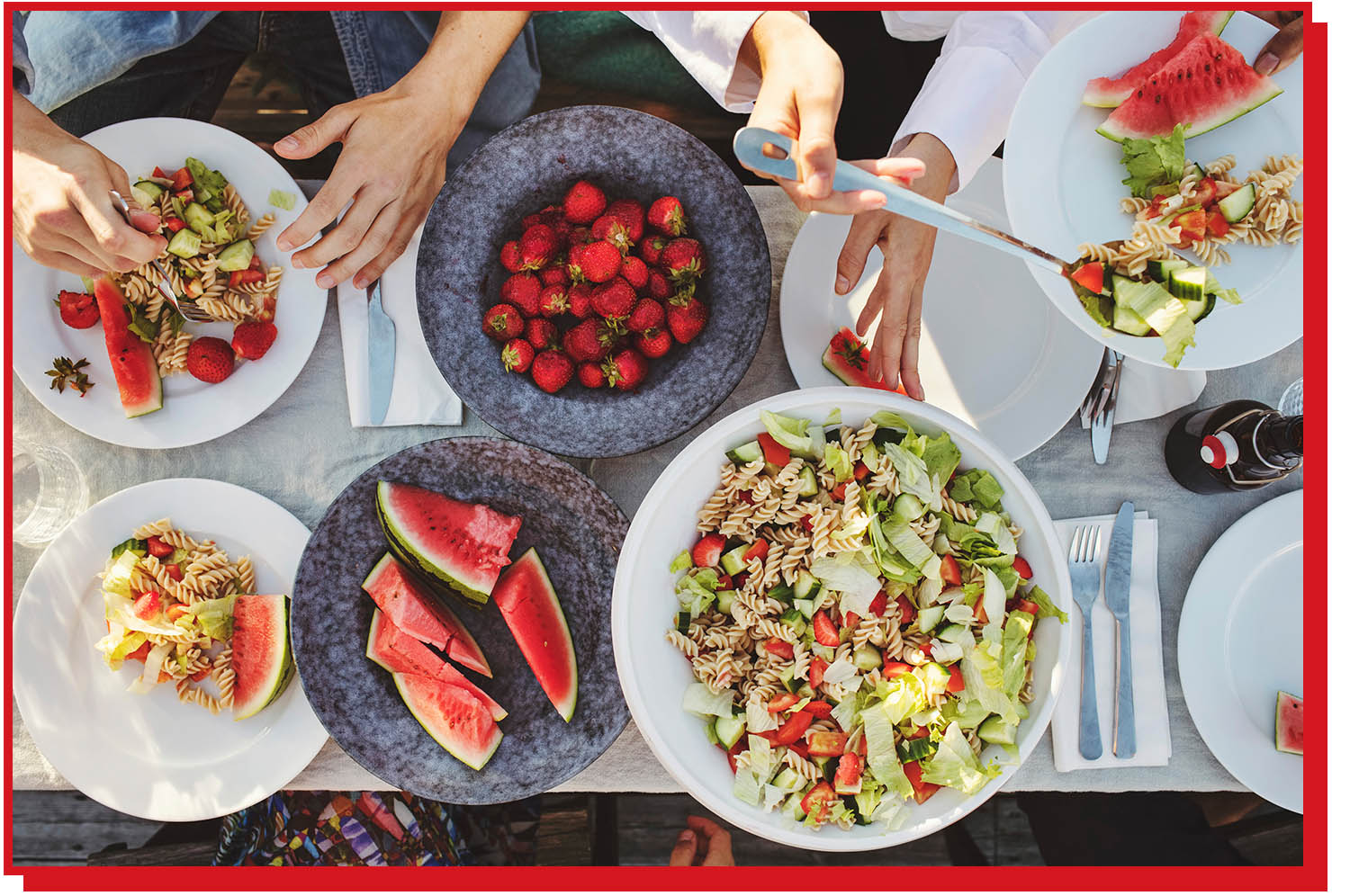 Overhead view of table with bowls of pasta salad, cut watermelon, and strawberries.