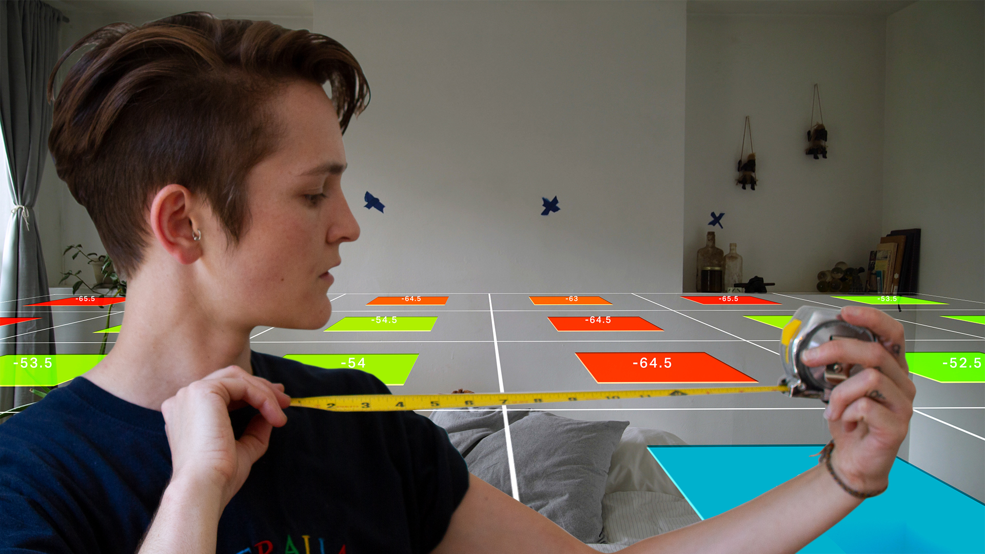 Video host uses tape measure in foreground; in background, a graphic grid representing wi-fi signal strength stretches across a room.
