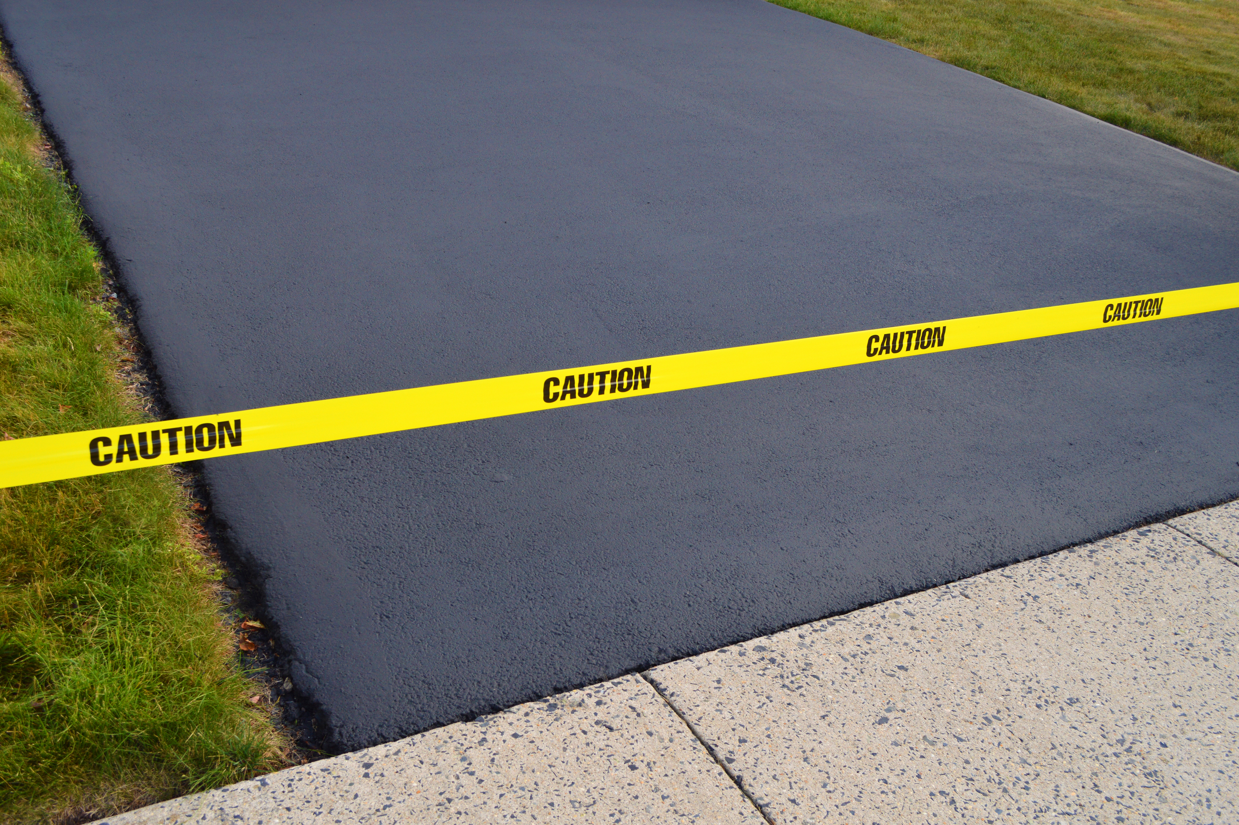 Caution tape at the end of a newly sealcoated driveway.