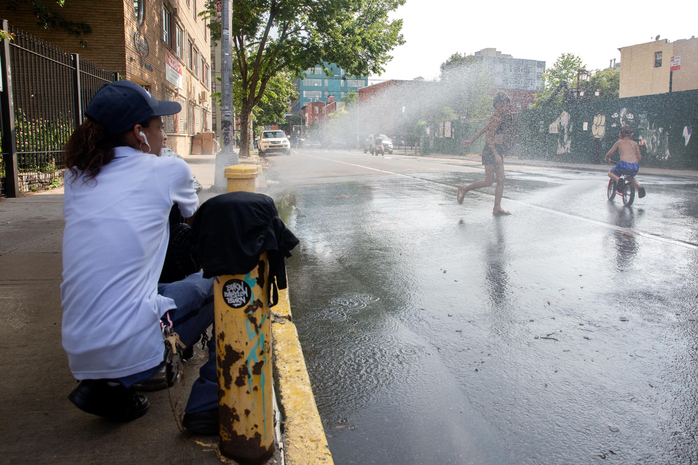 Tonya Gonzalez helps kids cool down on an open street in Williamsburg during the coronavirus outbreak, July 17, 2020.