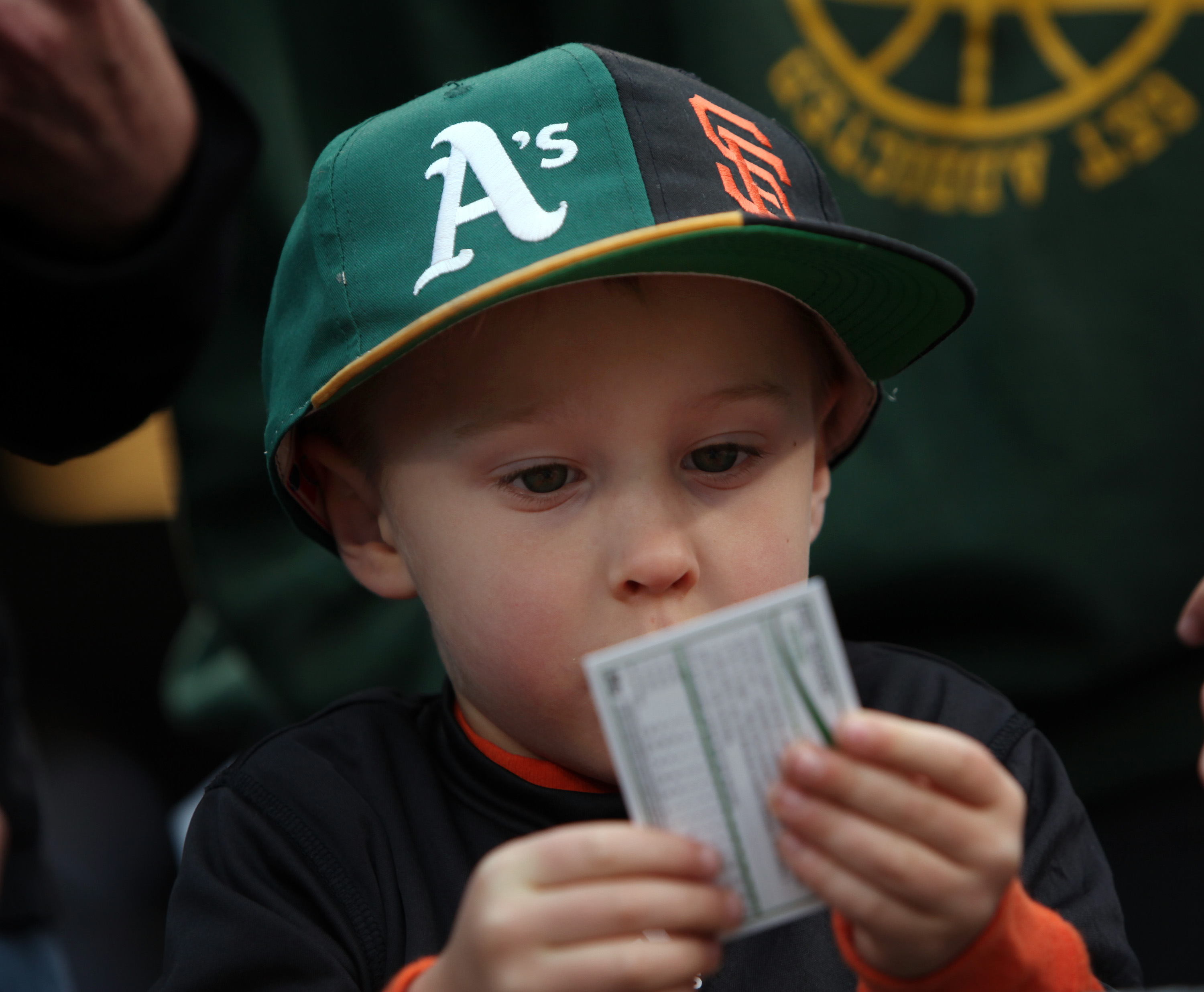Charlie Chesnosky, 3, of Burllingame, studies a baseball card while wearing his split bill A's-Giants hat before the first game of the Bay Bridge spring training series between the Oakland Athletics and the San Francisco Giants Thursday March 27, 2014, at