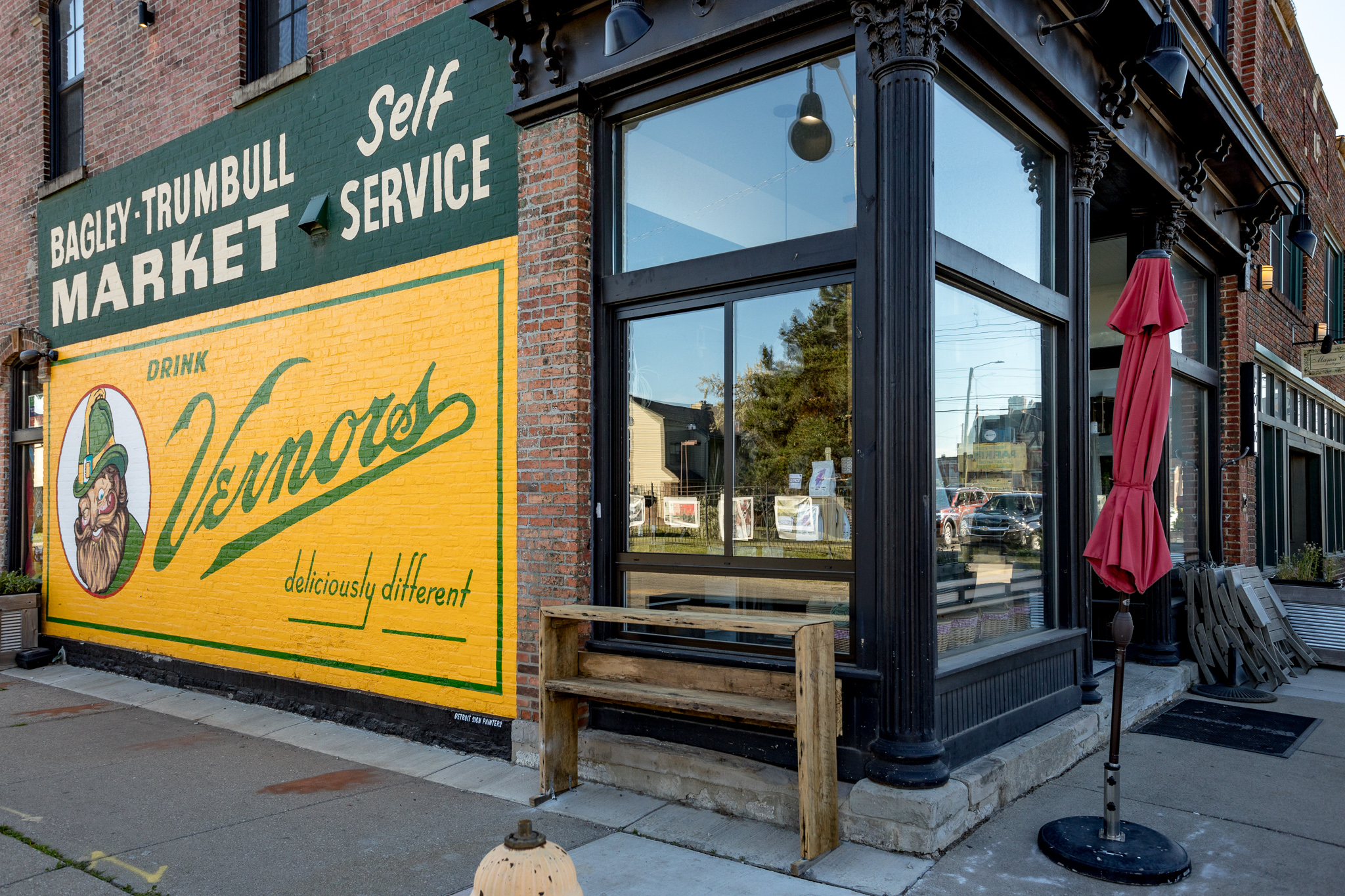 A painted sign for the old Bagley Trumbull Market and an advertisement for Vernor's flanks a newly installed walk-up window at Folk.