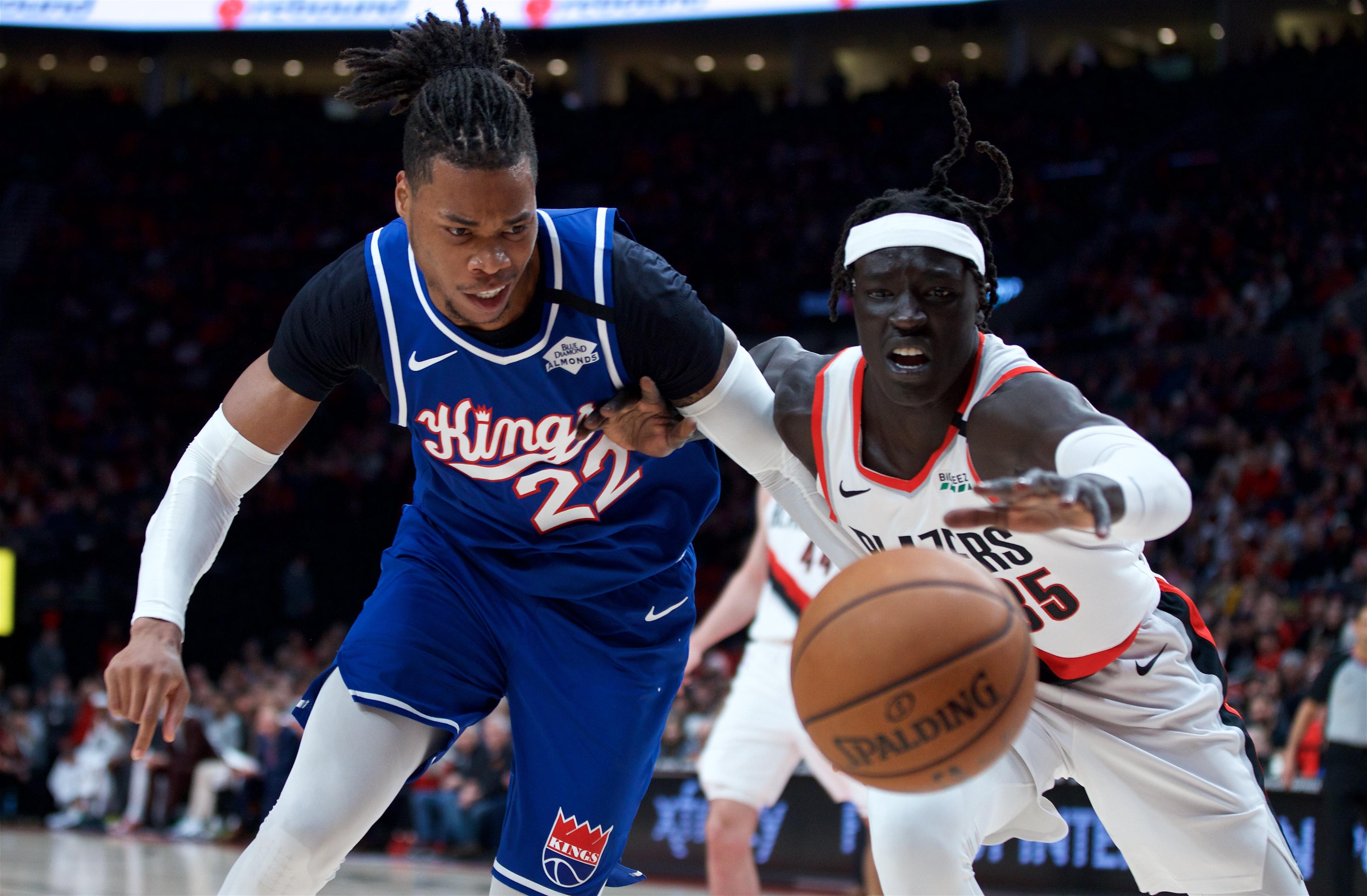 Sacramento Kings center Richaun Holmes and Portland Trail Blazers forward Wenyen Gabriel reach for a loose ball during the second quarter at the Moda Center.