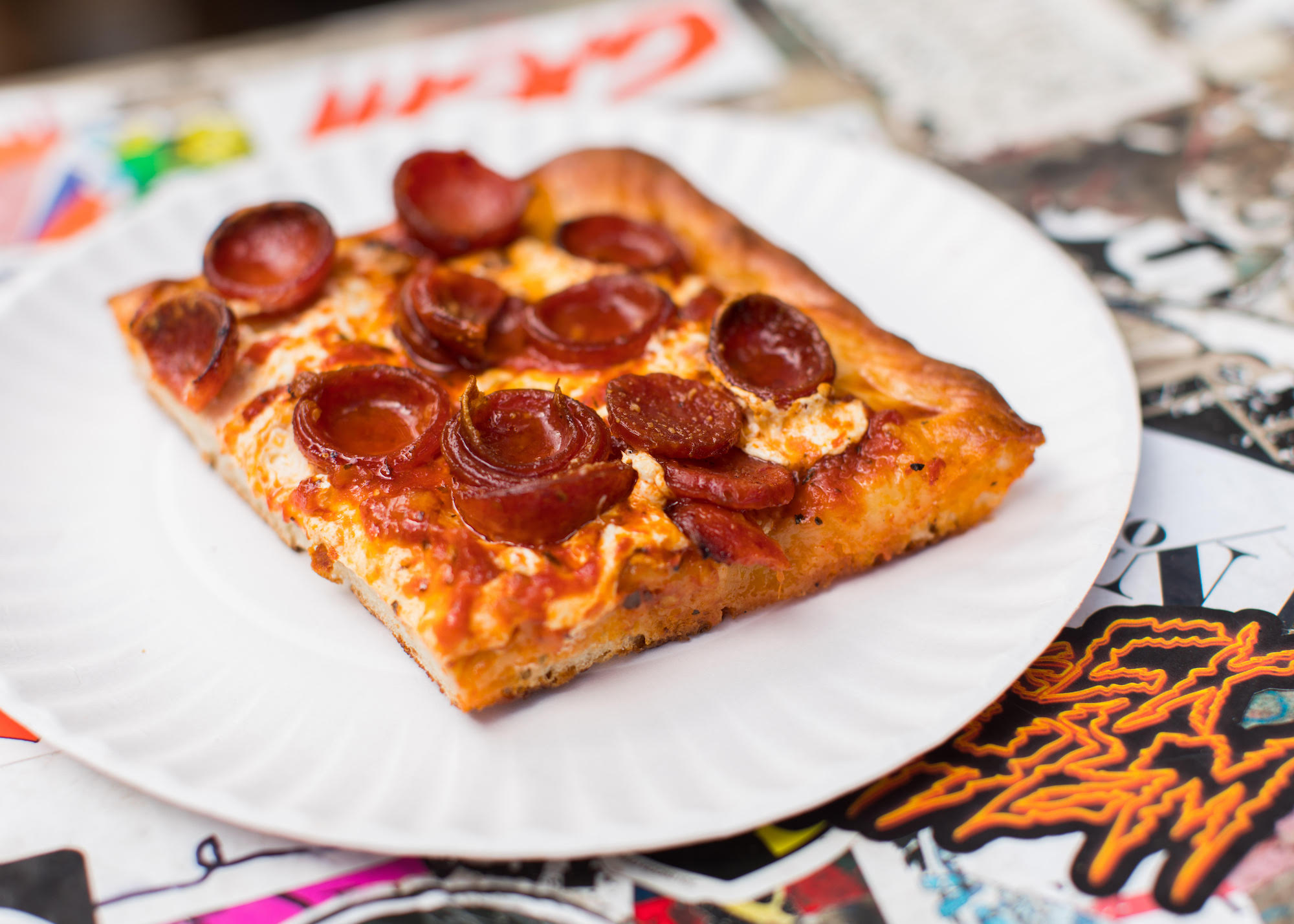 A square slice of pepperoni pizza with rolled-up cups and lots of cheese.