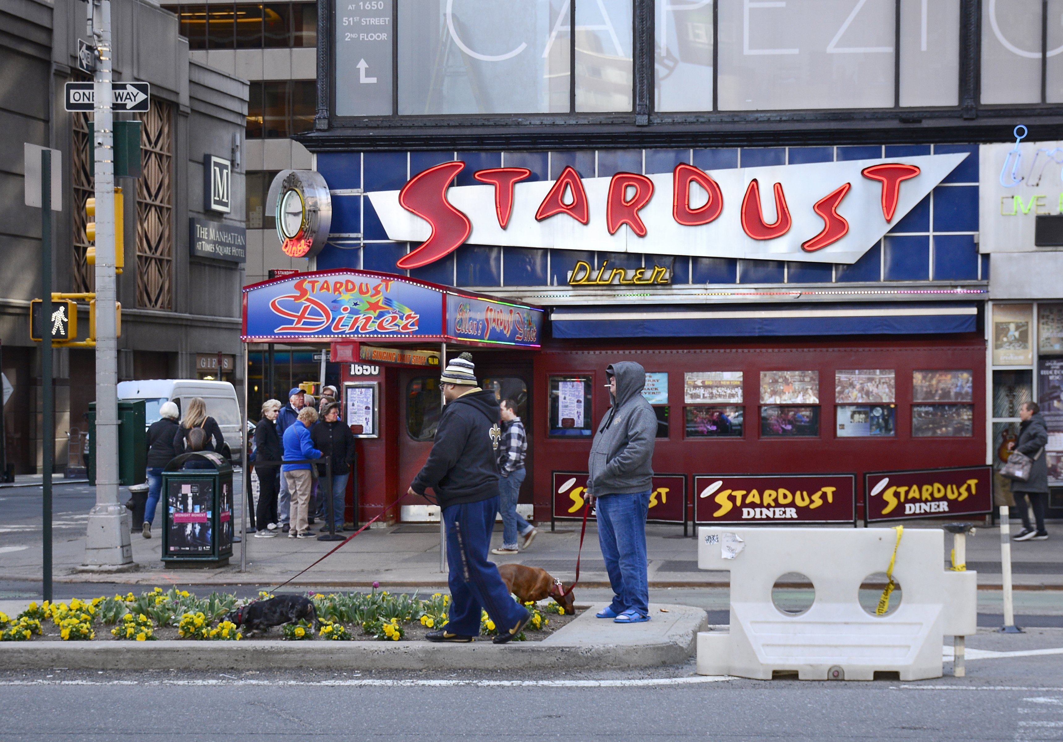 Two men walk their dogs in a flower bed as customers line up to enter the 1950s-themed Ellen's Stardust Diner on Broadway in New York City's Theater District.