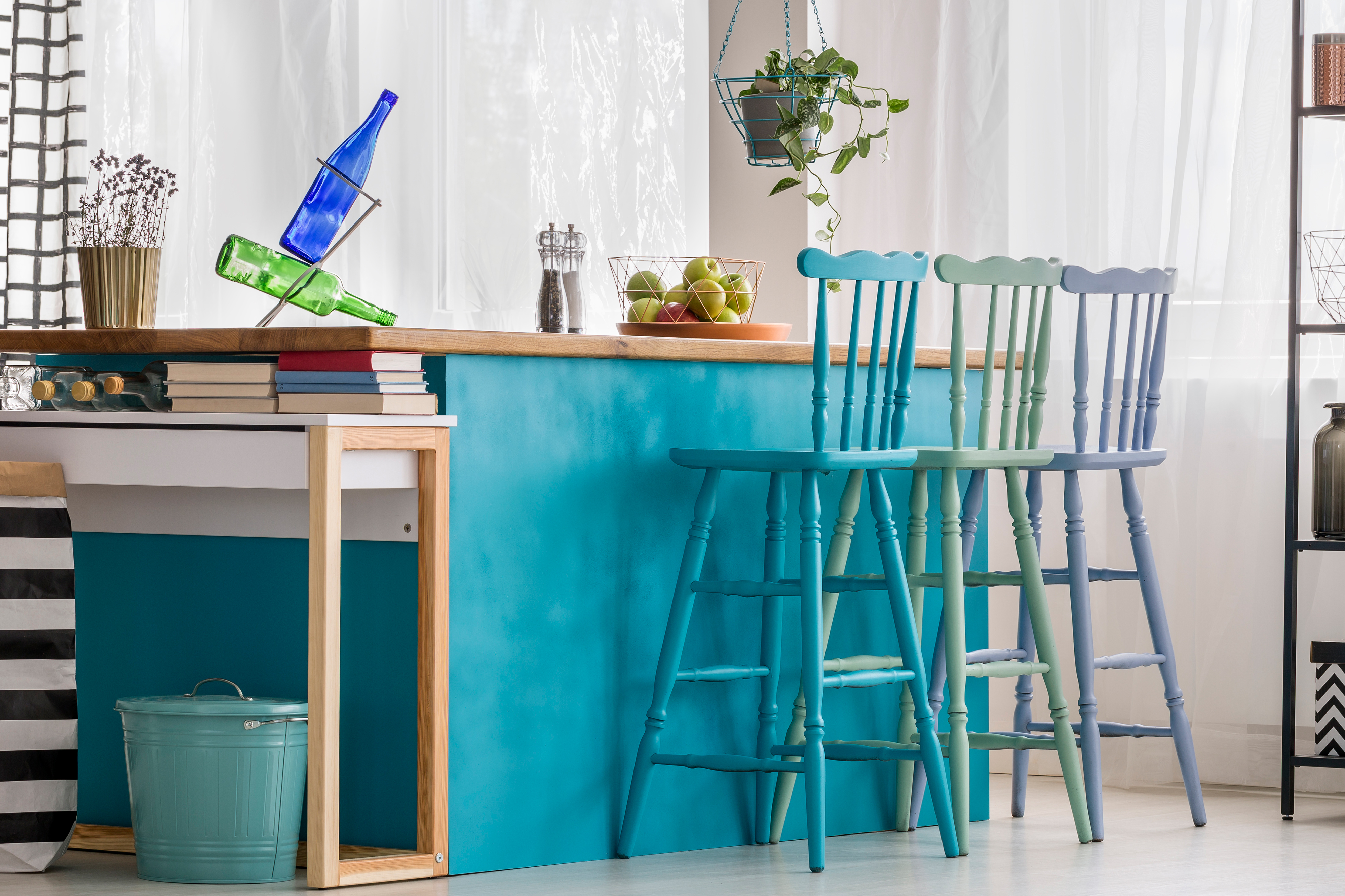 Blue, green and purple spray painted wood chairs in kitchen.